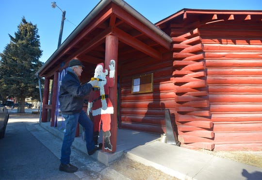 Ernie Lundberg, Lincoln Community Hall board president, hangs a Santa Claus decoration on Thursday afternoon.