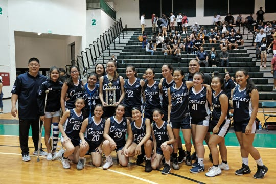 The Academy of Our Lady of Guam Cougars Girl's basketball team after the IIAAG championship game against the Saint Paul Christian School Warriors at the University of Guam Calvo Fieldhouse December 7, 2018.