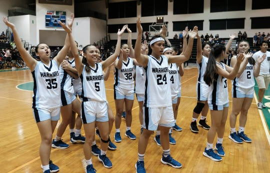 Saint Paul Christian School Warriors Girl's basketball team cheer to their fans after winning the IIAAG Girl's basketball championship game against the Academy of Our Lady of Guam Cougars at the University of Guam Calvo Field House in this Dec. 7, 2018, file photo.