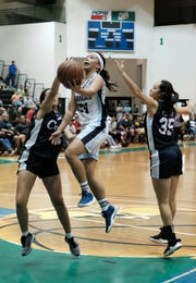 Saint Paul Christian School Warriors Niah Siguenza brings the ball towards the hoop through the AOLG Cougars defense during the IIAAG Girl's basketball championship game at the University of Guam Calvo Fieldhouse December 7, 2018. The Warriors won 51-34.