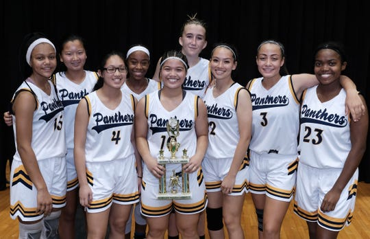 The Guam High Panthers hold the third place trophy after winning their game against the George Washington Geckos at the University of Guam Calvo fieldhouse December 7, 2018. The Panthers won 53-50.