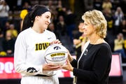 Iowa center Megan Gustafson is shown in December with her coach, Lisa Bluder, in a ceremony to honor Gustafson's 1,000th career rebound. On Saturday, the pair won the Naismith national player of the year and coach of the year honors.