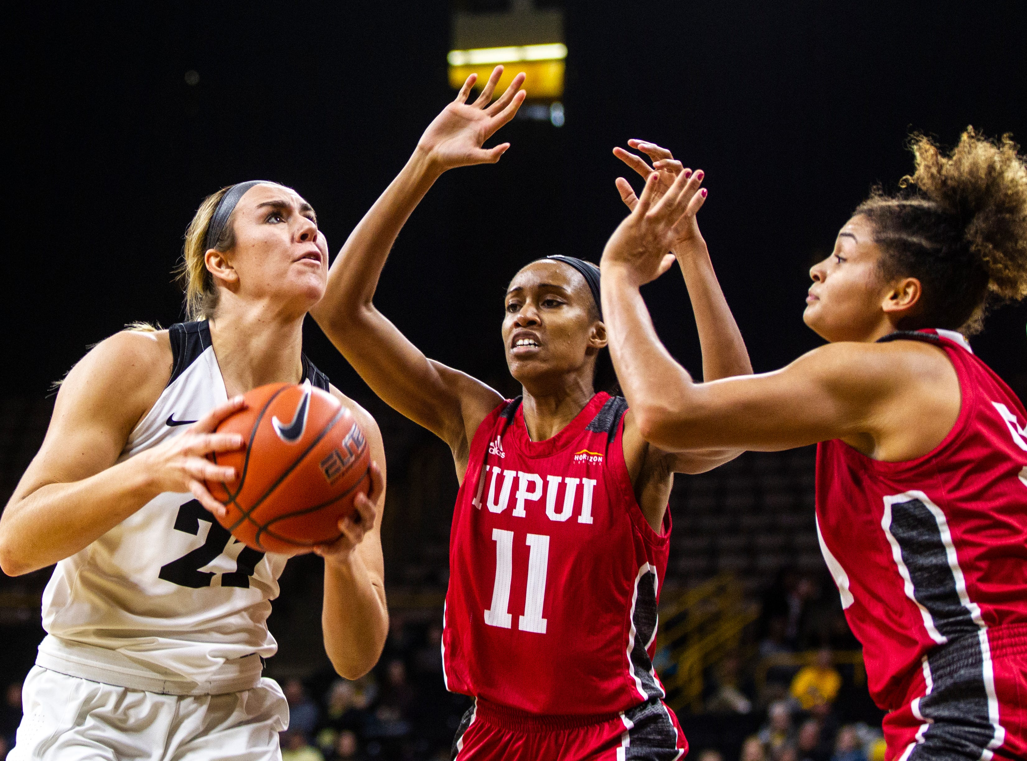 Iowa forward Hannah Stewart (21) attempts a basket while being defended by IUPUI's Tamya Sims (11) during a NCAA women's basketball game on Saturday, Dec. 8, 2018, at Carver-Hawkeye Arena in Iowa City.