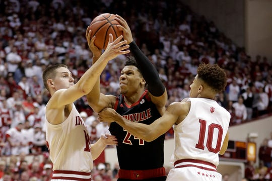 Louisville's Dwayne Sutton (24) goes to the basket against Indiana's Zach McRoberts (15) and Rob Phinisee (10) during the first half of an NCAA college basketball game, Saturday, Dec. 8, 2018, in Bloomington, Ind.