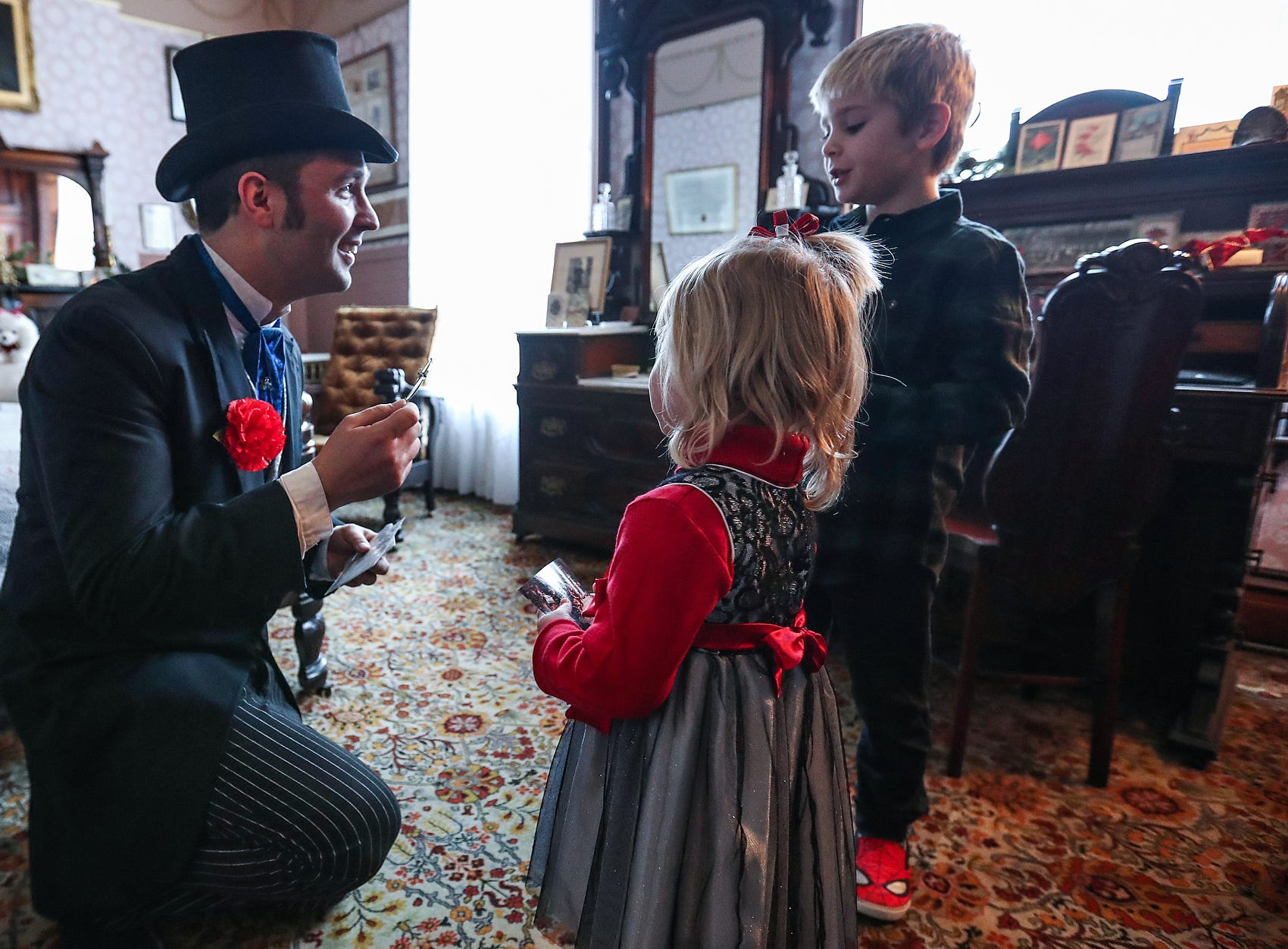 James Whitcomb Riley, portrayed by Chadwick Gillenwater, greets Nora Mize, 2, and Henry Mize, 6, during a Victorian Christmas open house at the James Whitcomb Riley museum home in Indianapolis, Saturday, Dec. 8, 2018.