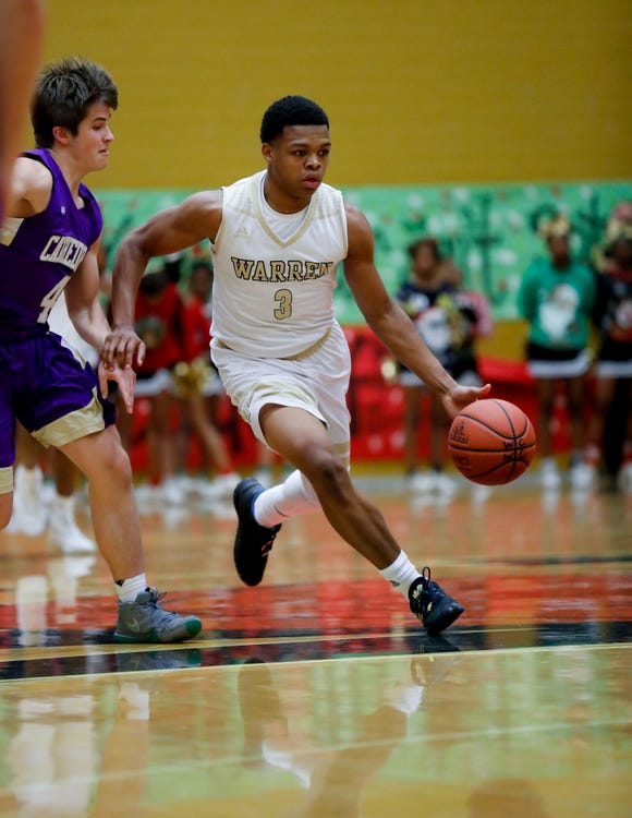 Warren Central High School's Manuel Brown (3) dribbles past Cathedral High School's Ryan Trusler (4) during a varsity boys basketball game between Cathedral High School and Warren Central High School at Warren Central on Friday, Dec. 7, 2018.