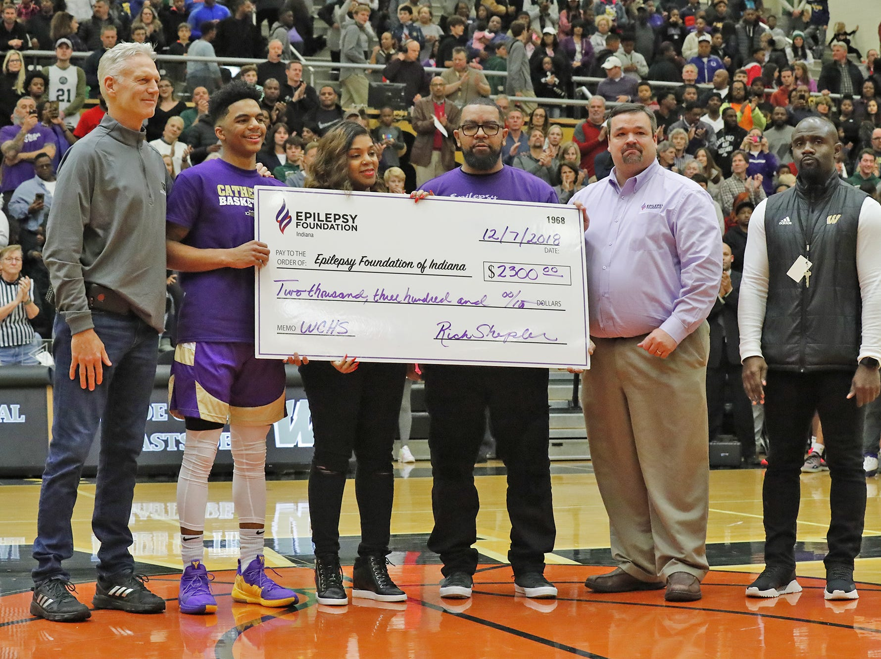 Left to right, Warren Central High School Principal, Rich Shepler,  Cathedral High School's James Franklin Jr., his parents Tamika and James Franklin Sr., and Ryan Keys, a representative from the Indiana Epilepsy Foundation, and Warren Central Athletic Director Marques Clayton, take the court for a check presentation to the Epilepsy Foundation on behalf of James Franklin Jr. who suffers from the disease, before a game between Cathedral High School and Warren Central High School, at Warren Central on Friday, Dec. 7, 2018.