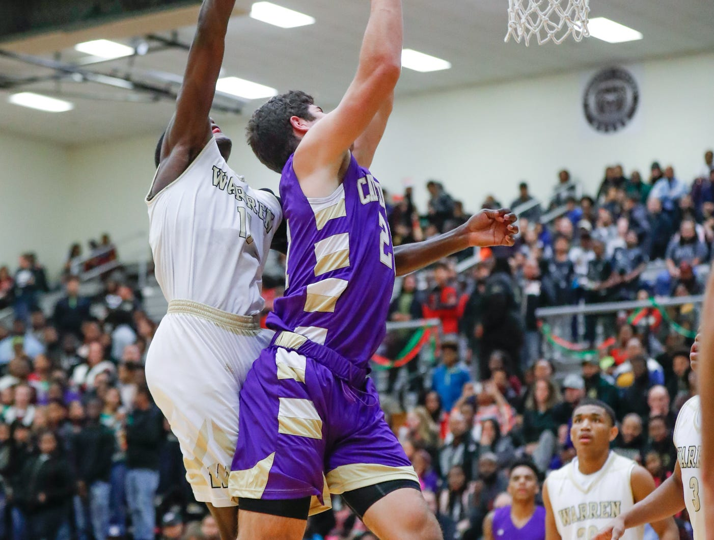 Cathedral High School's Isaac Farah (34) shoots past Warren Central High School's forward Jesse Bingham (11) to the hoop during a varsity boys basketball game between Cathedral High School and Warren Central High School at Warren Central on Friday, Dec. 7, 2018.