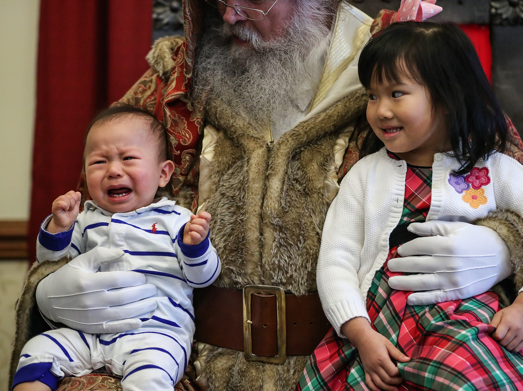 From left, Andrew Ho, 1, cries on Santa's lap while his sister Catherine Ho, 5, looks on, during a Victorian Christmas open house at the James Whitcomb Riley museum home and Billie Lou Wood visitor center in Indianapolis, Saturday, Dec. 8, 2018.