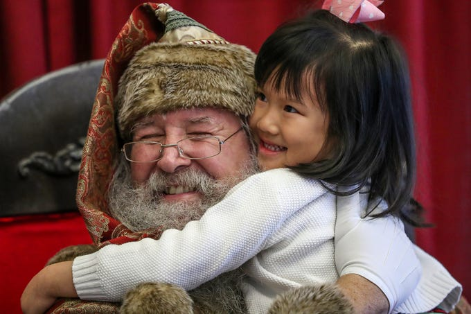 Catherine Ho, 5, hugs Santa Claus after visiting him during a Victorian Christmas open house at the James Whitcomb Riley museum home and Billie Lou Wood visitor center in Indianapolis, Saturday, Dec. 8, 2018.