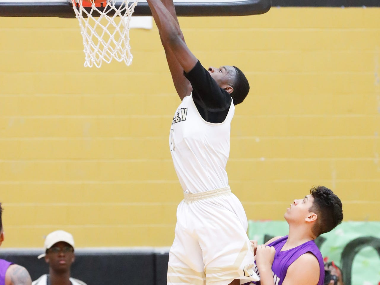 Warren Central High School's forward Jesse Bingham (11) hits a big dunk over Cathedral High School's Isaac Farah (34), during a varsity boys basketball game between Cathedral High School and Warren Central High School at Warren Central on Friday, Dec. 7, 2018.