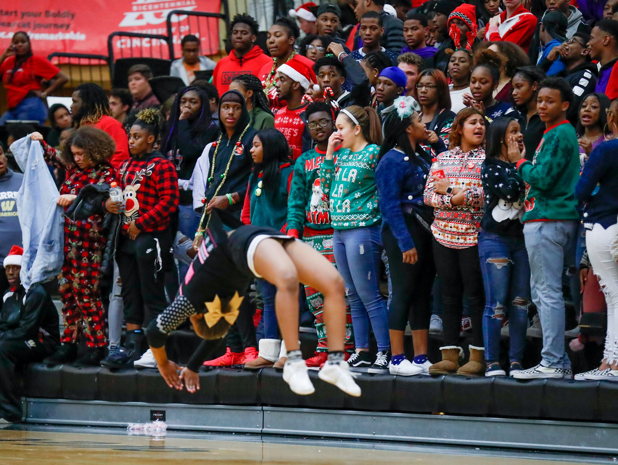 A cheerleader tumbles while wearing an ugly Christmas Sweater during a varsity boys basketball game between Cathedral High School and Warren Central High School at Warren Central on Friday, Dec. 7, 2018.