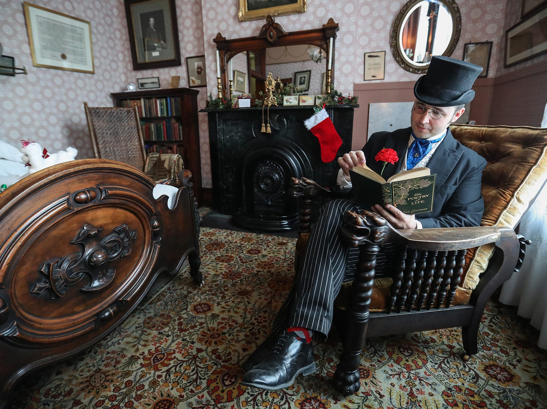 Chadwick Gillenwater poses for a portrait while portraying James Whitcomb Riley in the writer's historic museum home, decorated for a Victorian Christmas open house in Indianapolis, Saturday, Dec. 8, 2018.