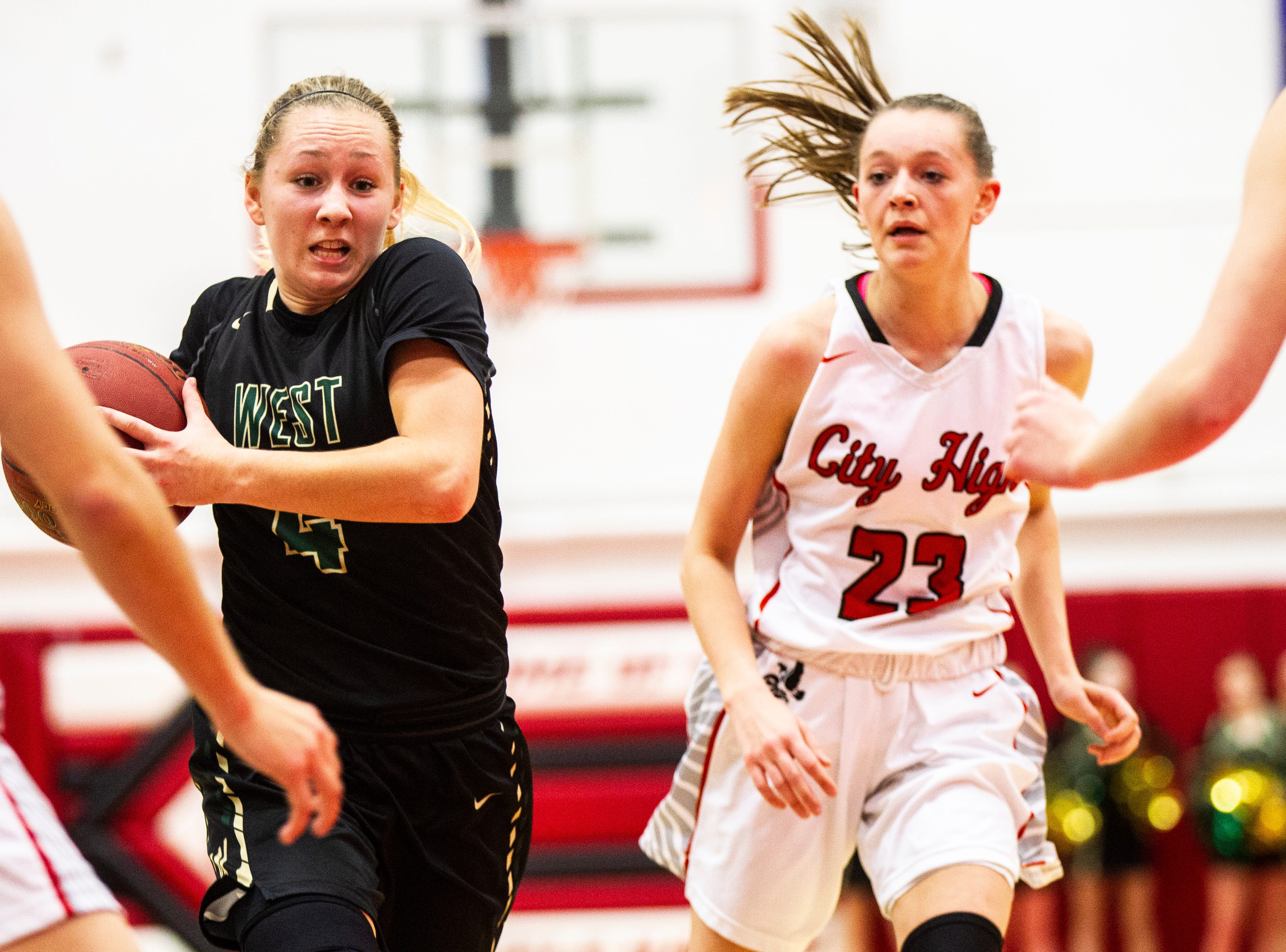 Iowa City West's Lauren Zacharias (4) takes the ball up court while being defended by Iowa City High's Aubrey Joens (23) during a Class 5A girls basketball game on Friday, Dec. 7, 2018, at City High School in Iowa City.