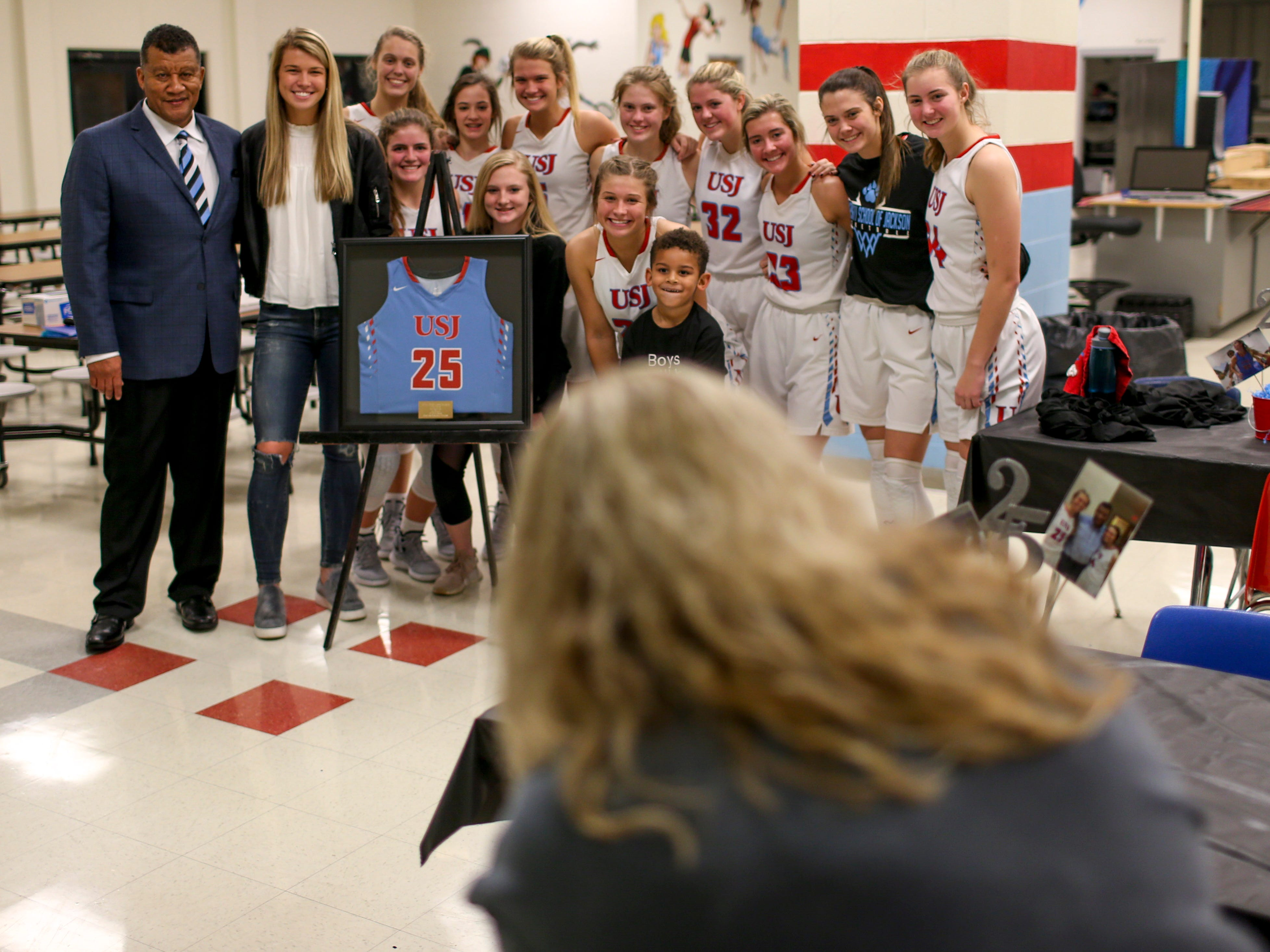 Anna Jones poses for photos with Tony Schutes and the current USJ girls basketball team at University School of Jackson in Jackson, Tenn., on Friday, Dec. 7, 2018.