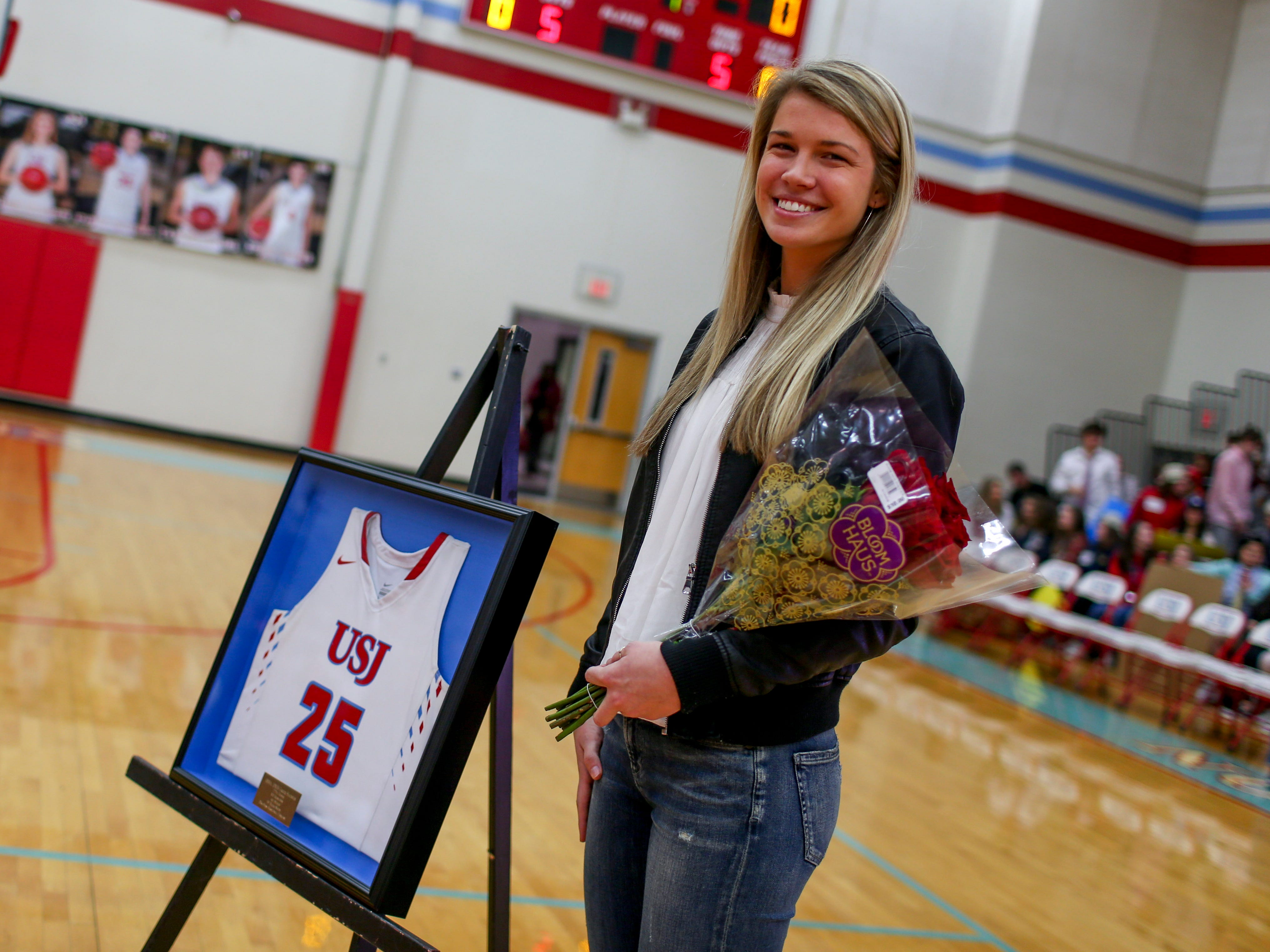 Anna Jones smiles next to her old jersey that can be seen in a frame during the retirement ceremony of her old jersey number 25 at University School of Jackson in Jackson, Tenn., on Friday, Dec. 7, 2018.