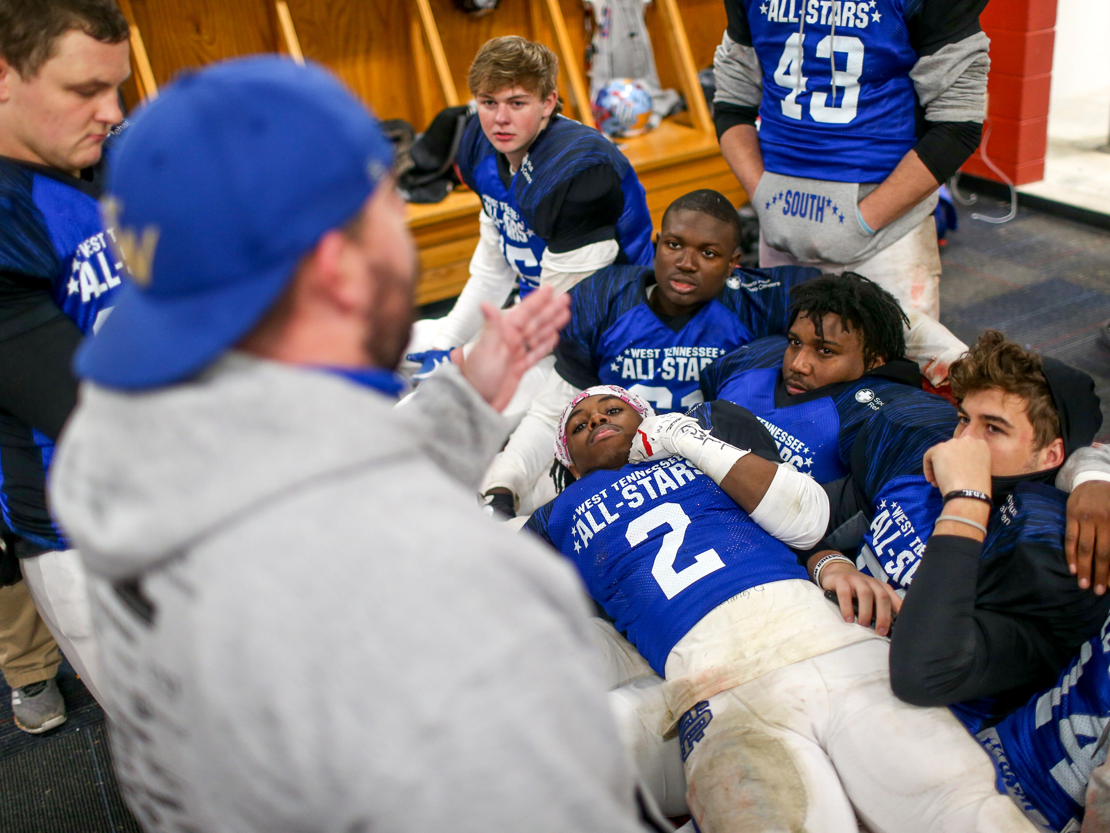 Peabody's Courtlen Wade (2) lays down across his teammates while listening to their coach speak to them at halftime during the West Tennessee All-Star football game at University School of Jackson in Jackson, Tenn., on Friday, Dec. 7, 2018.