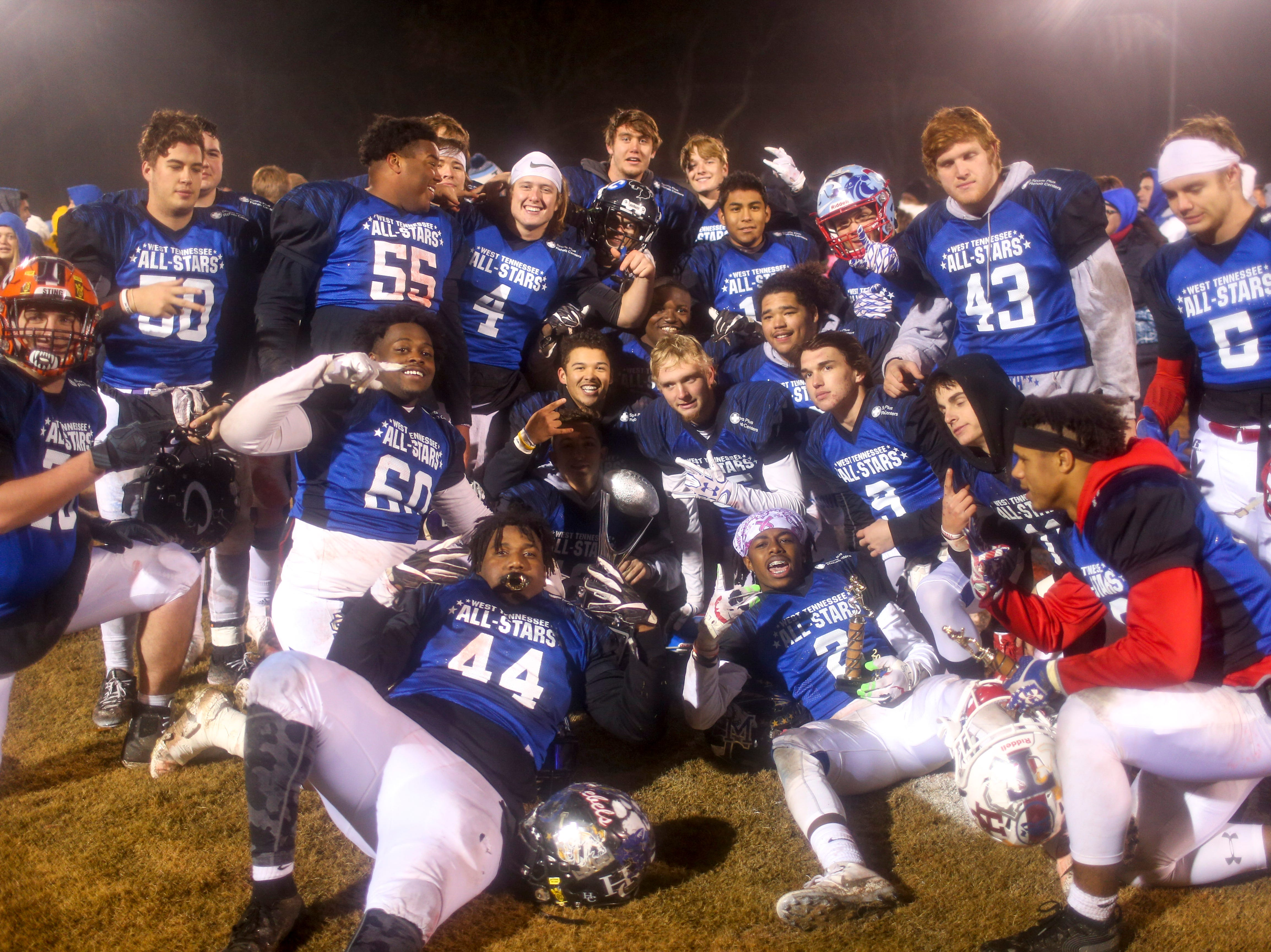 South players mesh together for a photo with the trophy after winning the West Tennessee All-Star football game at University School of Jackson in Jackson, Tenn., on Friday, Dec. 7, 2018.