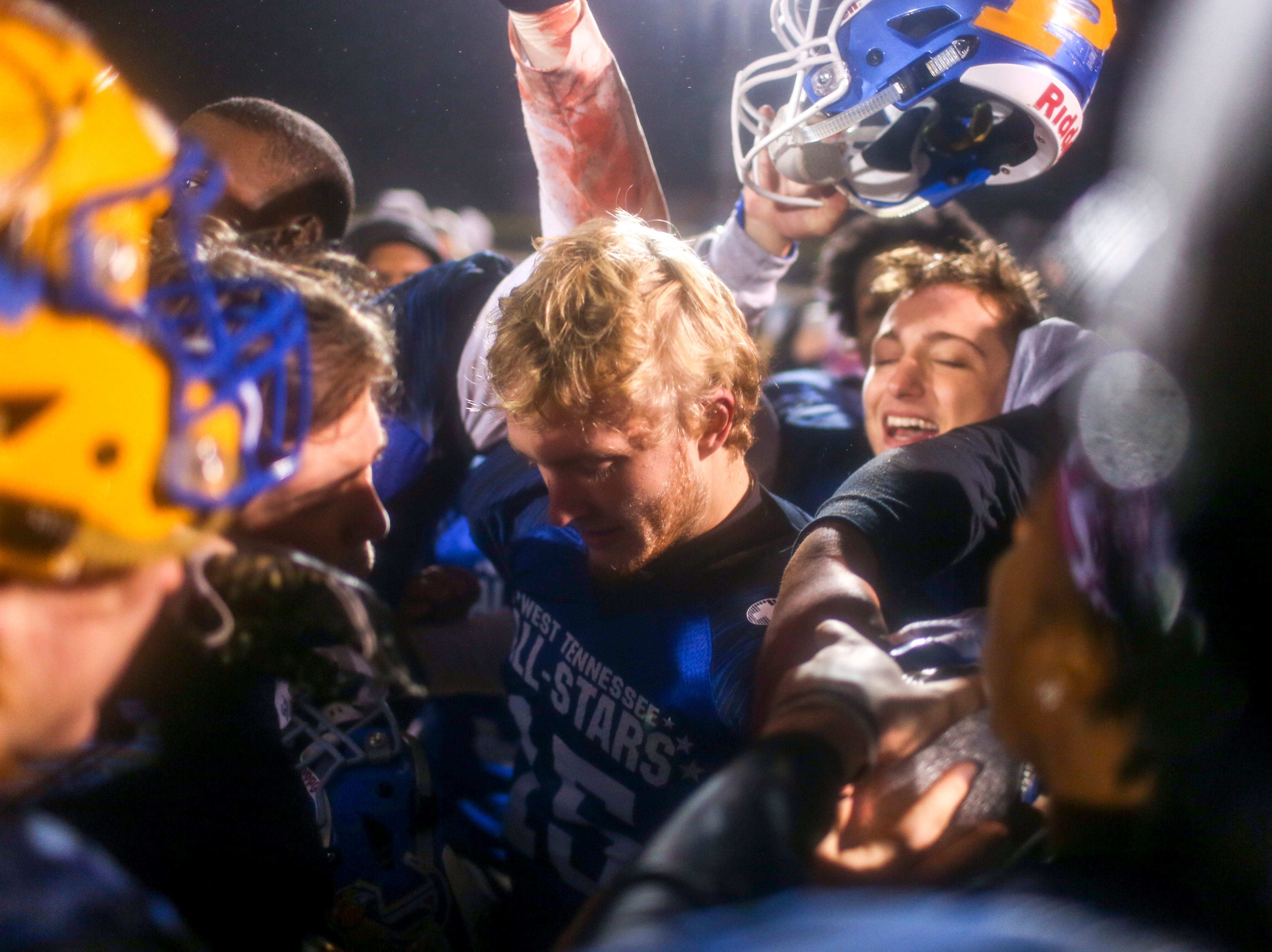 South players gather around and celebrate with the trophy during the West Tennessee All-Star football game at University School of Jackson in Jackson, Tenn., on Friday, Dec. 7, 2018.