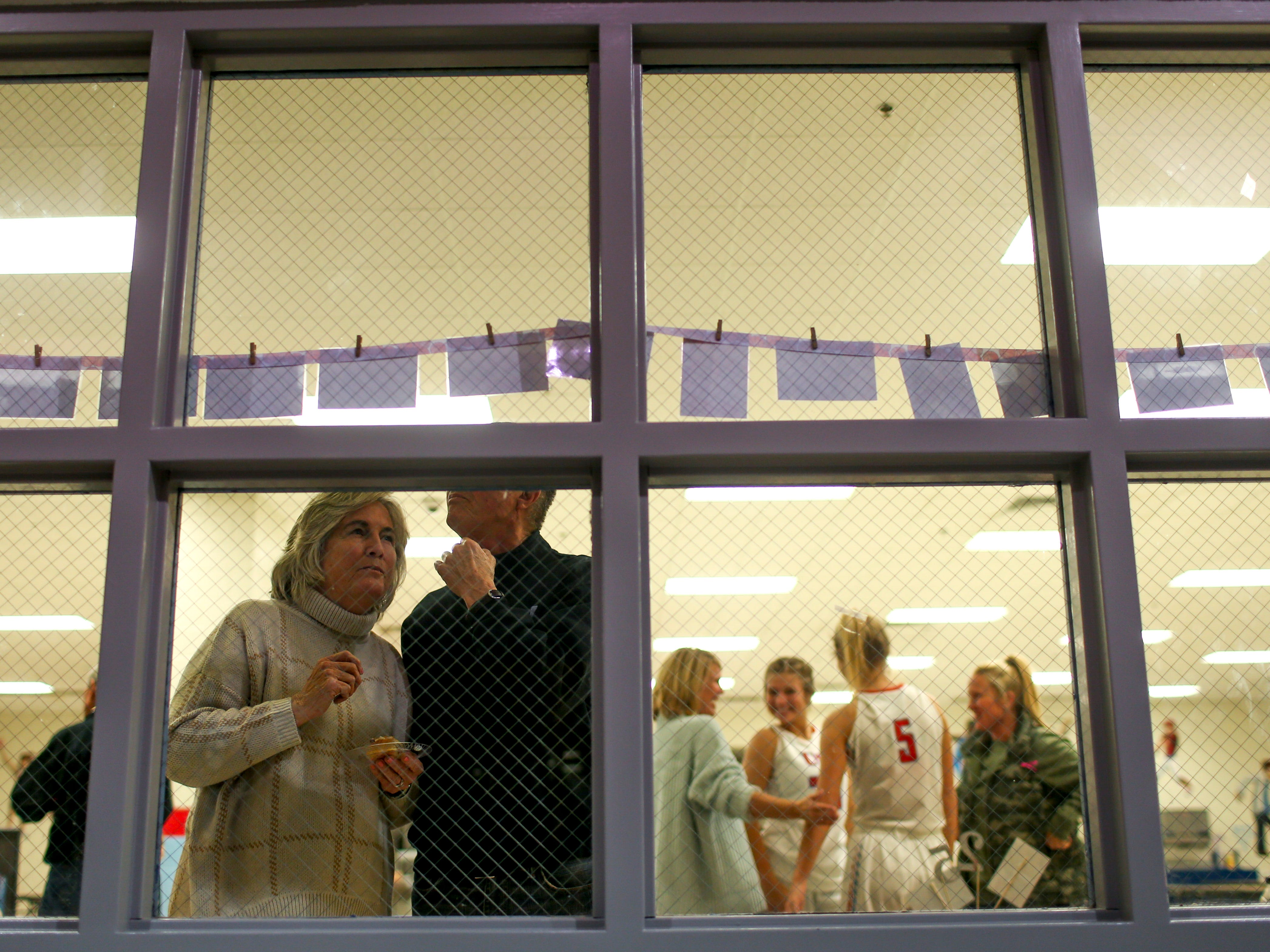 Visitors to the jersey number 25 retirement party examine old photos of Anna Jones strung up in the window at University School of Jackson in Jackson, Tenn., on Friday, Dec. 7, 2018.