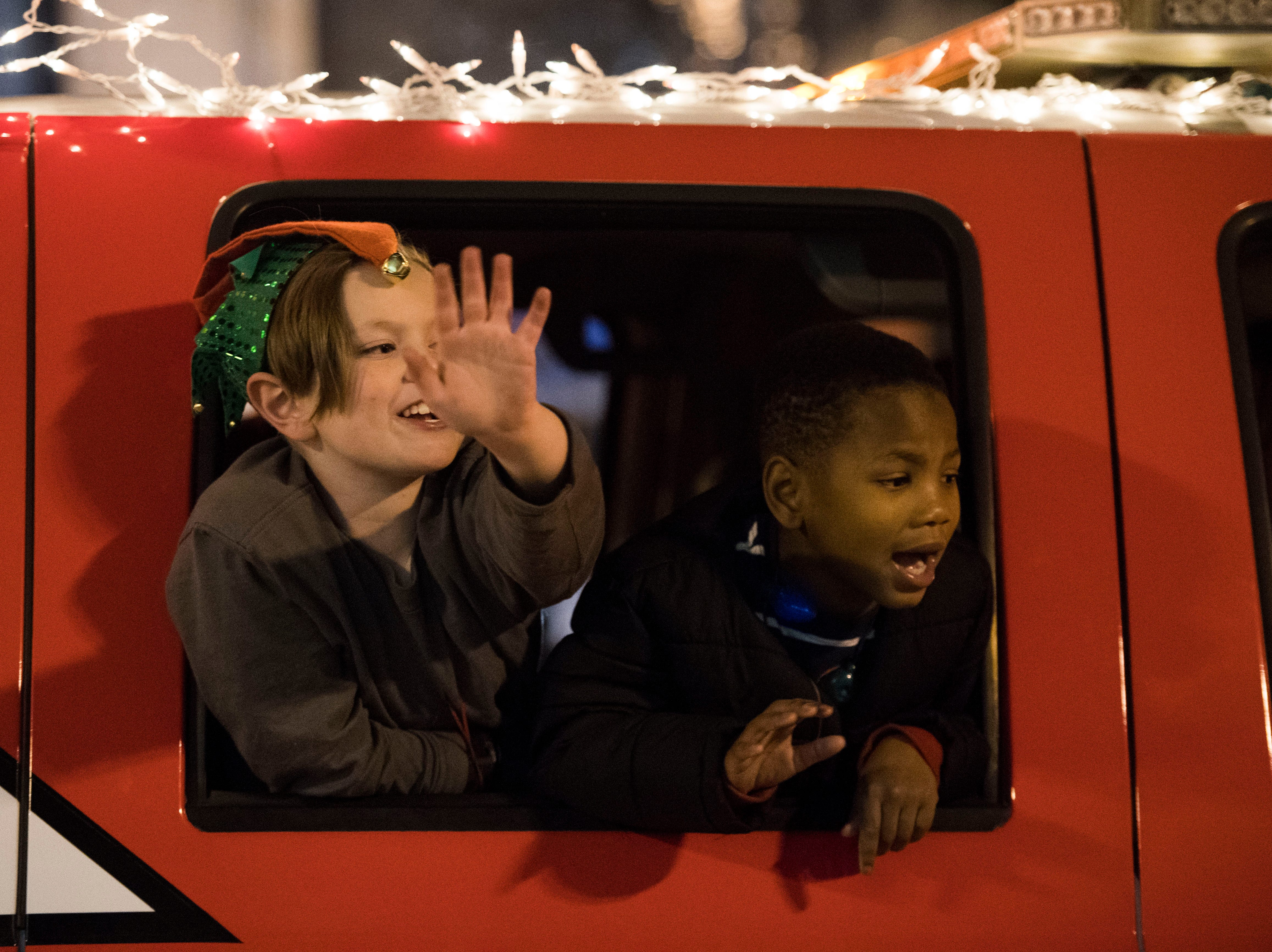 Children wave to spectators during the annual WIVK Christmas Parade in downtown Knoxville Friday, Dec. 7, 2018.