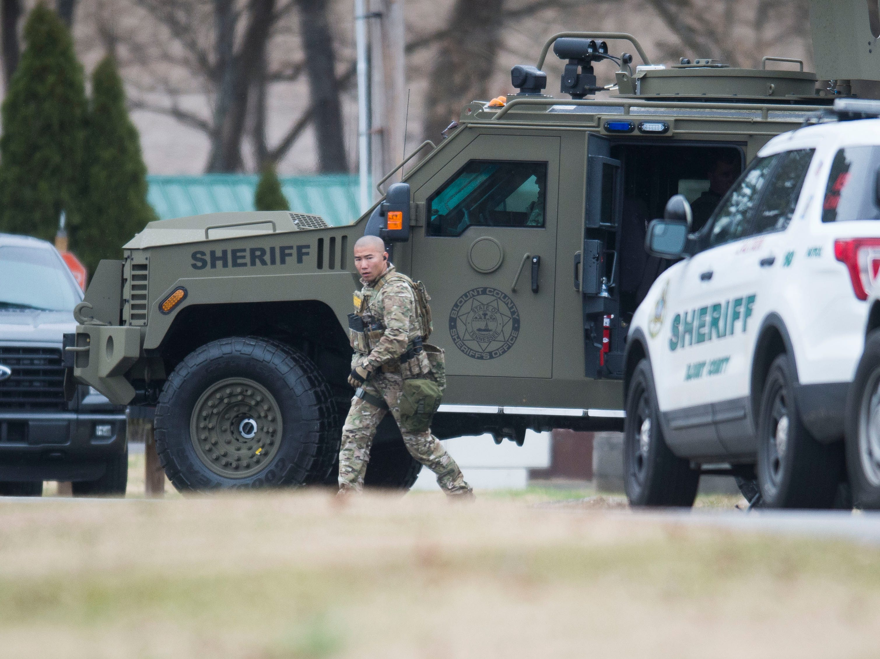 A Blount County Sheriff's officer walks outside an apartment building during a standoff involving one person believed to be armed at Riverside Manor Apartments Saturday, Dec. 8, 2018.