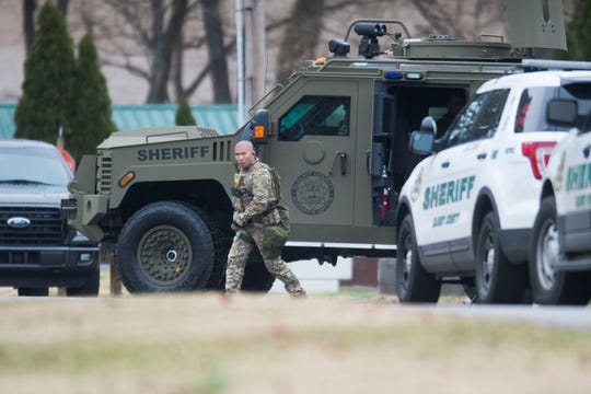 A Blount County Sheriff's officer walks outside an apartment building during a fatal standoff at Riverside Manor Apartments on Saturday.