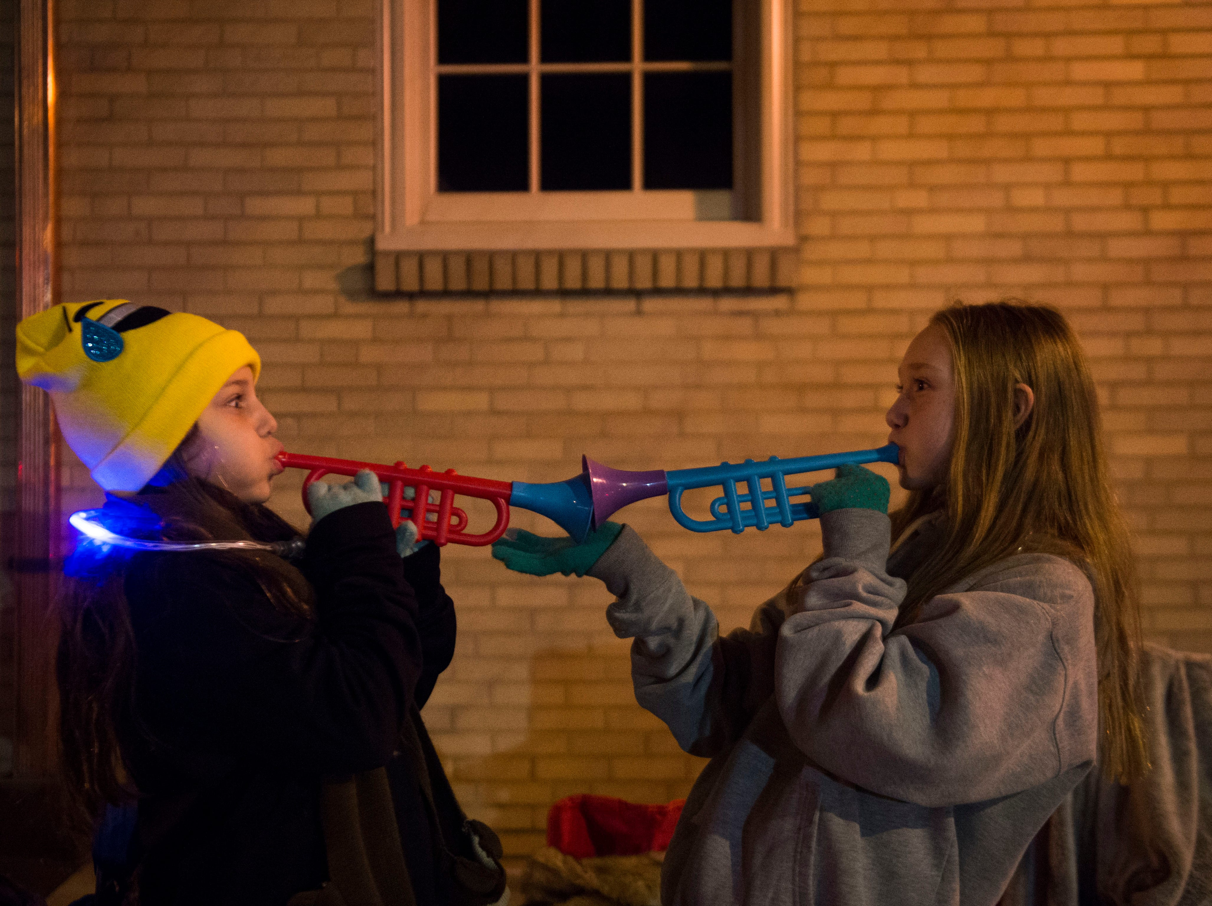 From left Sydney Harbeston, 9, and Lyla Tharp, 9, both of Knoxville, play with toy horns before the annual WIVK Christmas Parade in downtown Knoxville Friday, Dec. 7, 2018.