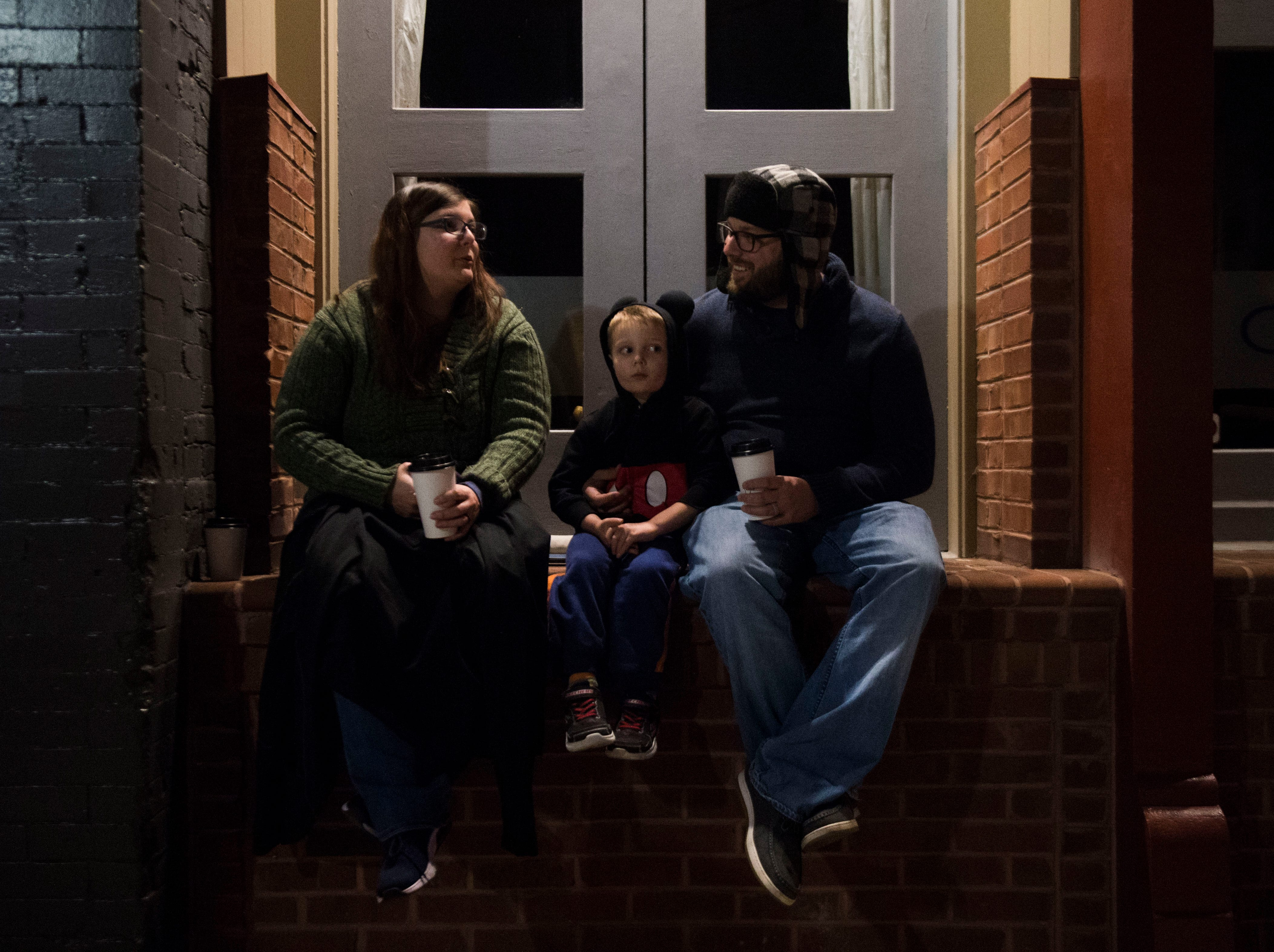 Megan Hill sits with her son Ollie, 4, and husband Adam during the annual WIVK Christmas Parade in downtown Knoxville Friday, Dec. 7, 2018.