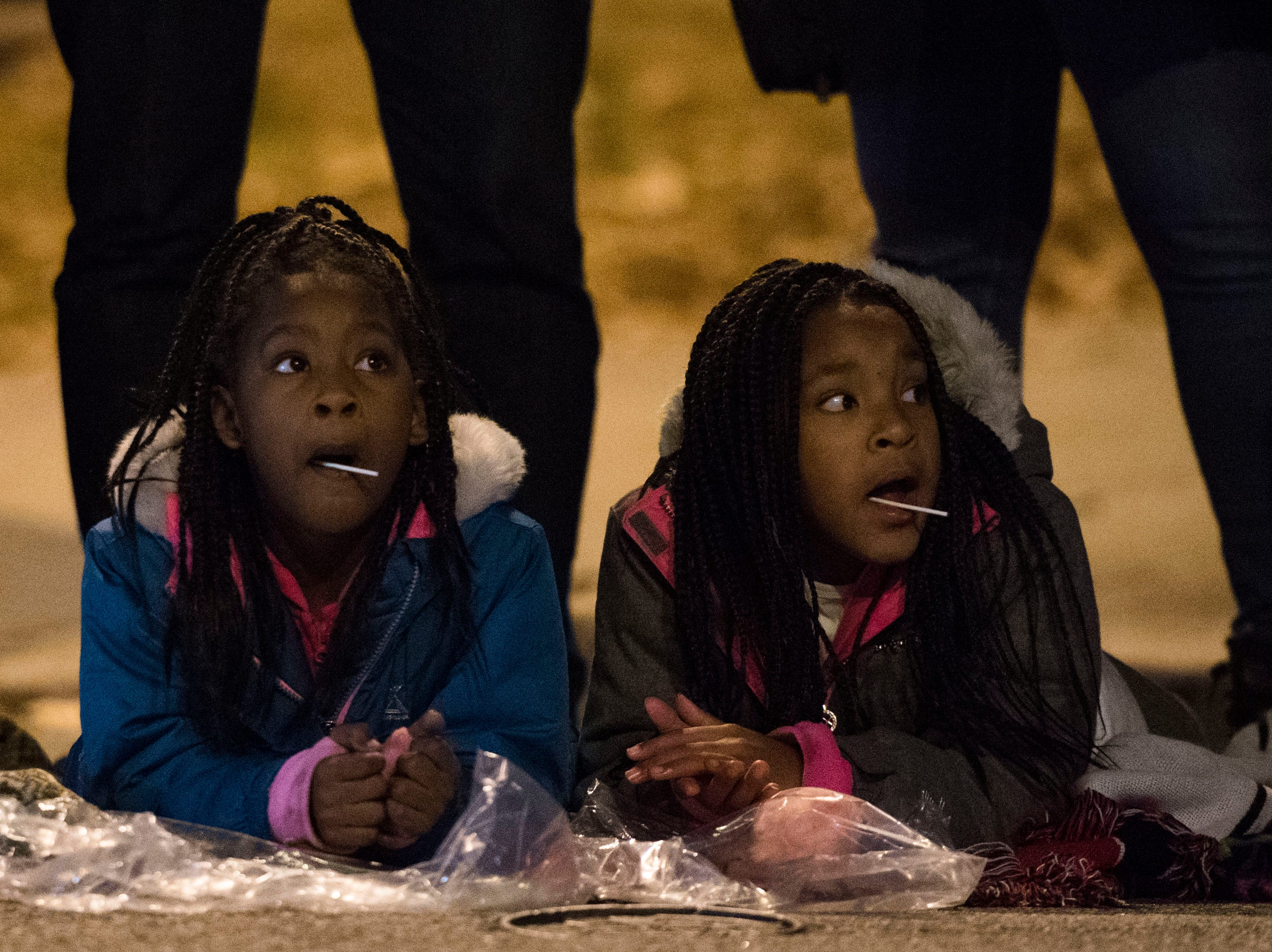 From left sisters Sydnee Douglas, 7, and Englynn, 8, both of Knoxville watch the annual WIVK Christmas Parade in downtown Knoxville Friday, Dec. 7, 2018.