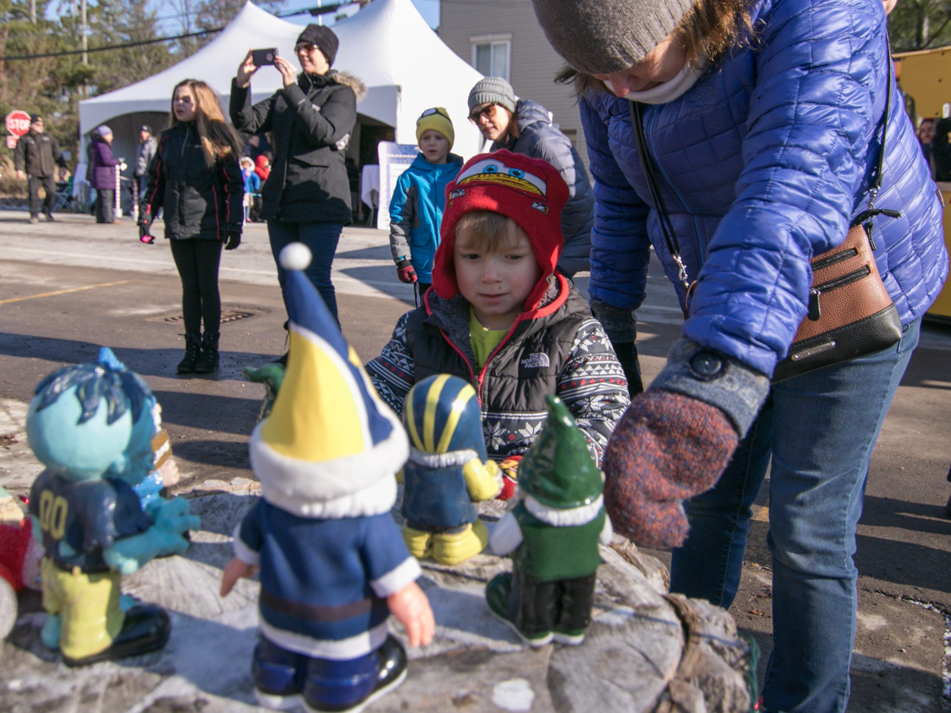 3-year-old Hunter Zurek and grandmother Marilyn Zurek look at gnomes displayed on a stump along Avon St. in Hartland for Polar Express Day Saturday, Dec. 8, 2018.