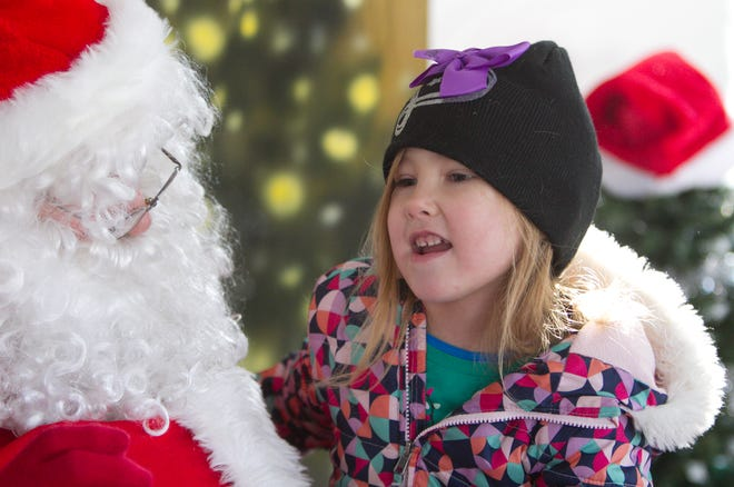 Adelyn Heinsch tells Santa she wants a puppy for Christmas at Hartland's Polar Express Day Saturday, Dec. 8, 2018.
