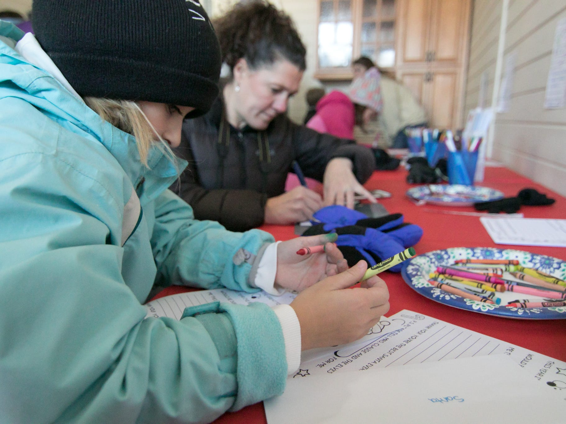 9-year-old Brynn Sargeant composes a letter to Santa as Brynn's friend's mom Summer Korponic addresses the envelope inside Village Real Estate Group for Polar Express Day Saturday, Dec. 8, 2018.