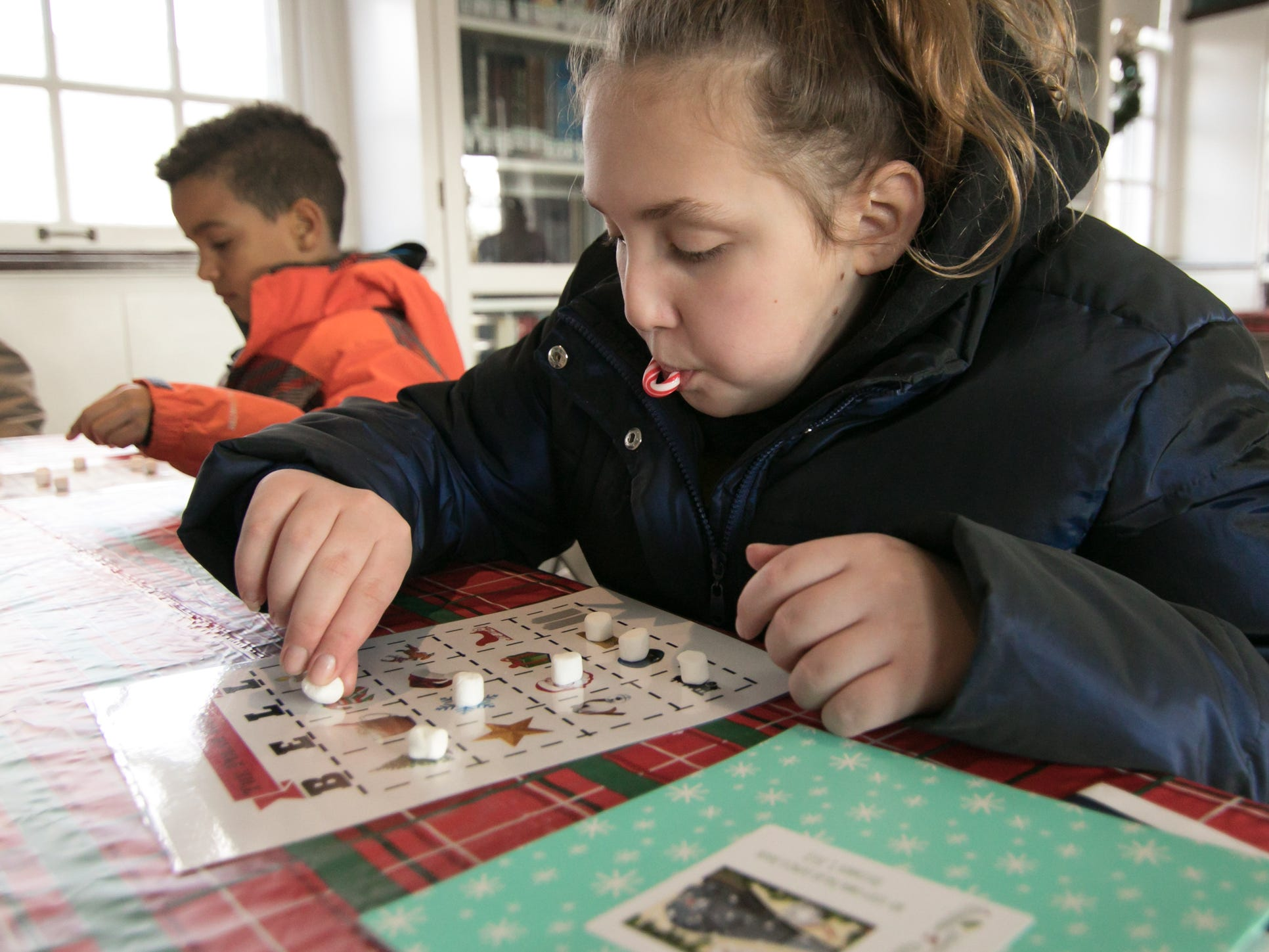 12-year-old Morgan Bertovick plays Bell Bingo with brother 7-year-old Josh Kesselring Saturday, Dec. 8, 2018 in the Hartland Cromaine Library during the Polar Express event.
