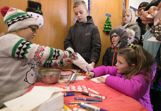 11-year-old Shea Lenhard, left, fills the bag of 10-year-old William Edie-Sabuda with magic reindeer feed as 8-year-old Jade Korponic composes a letter to the reindeer inside Ore Creek Veterinary Clinic as part of Polar Express Day Saturday, Dec. 8, 2018.