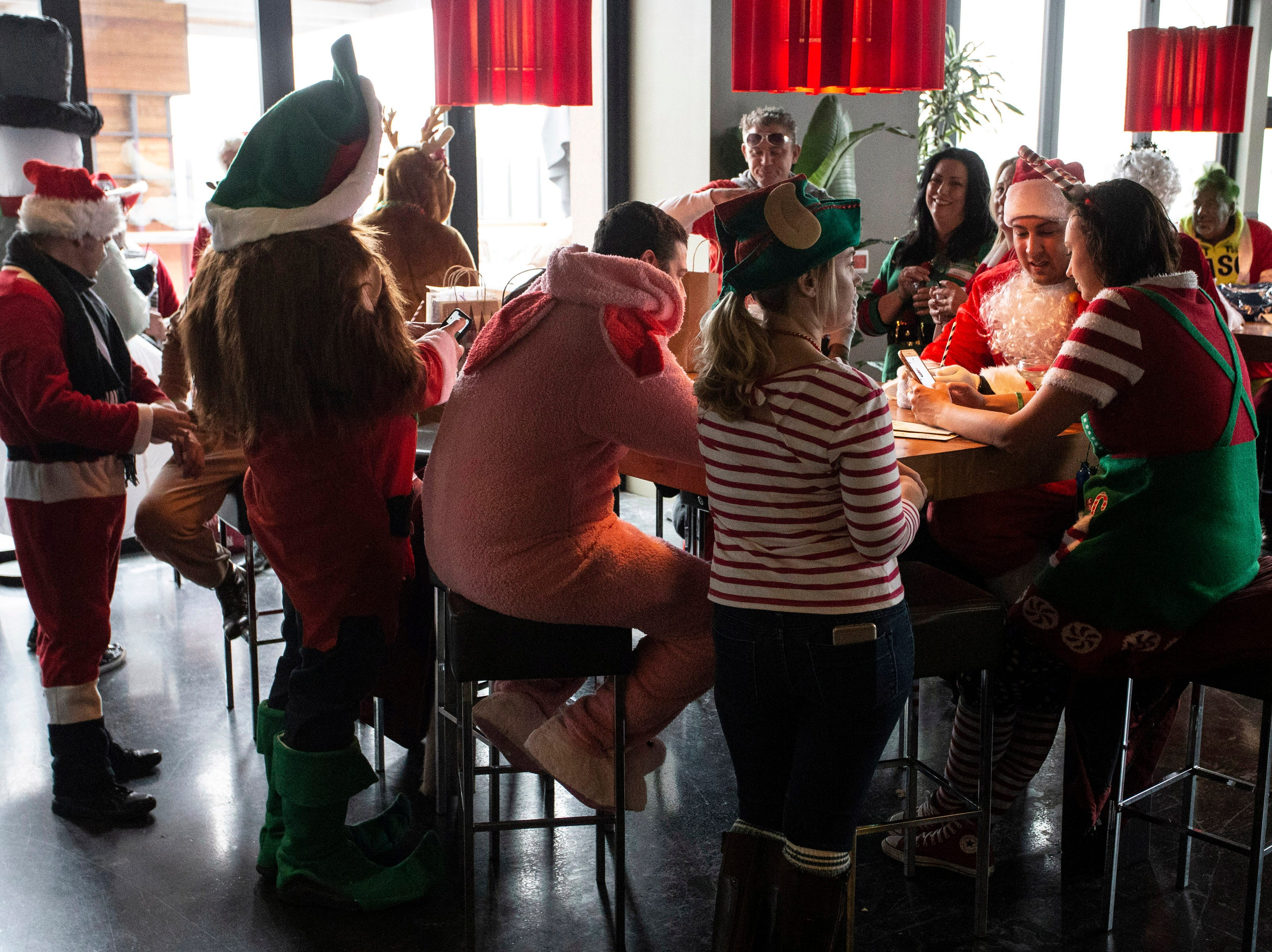 A variety of Santas and other holiday themed characters waited at 8UP to hear where the first stop on SantaCon would be Saturday. 12/8/18