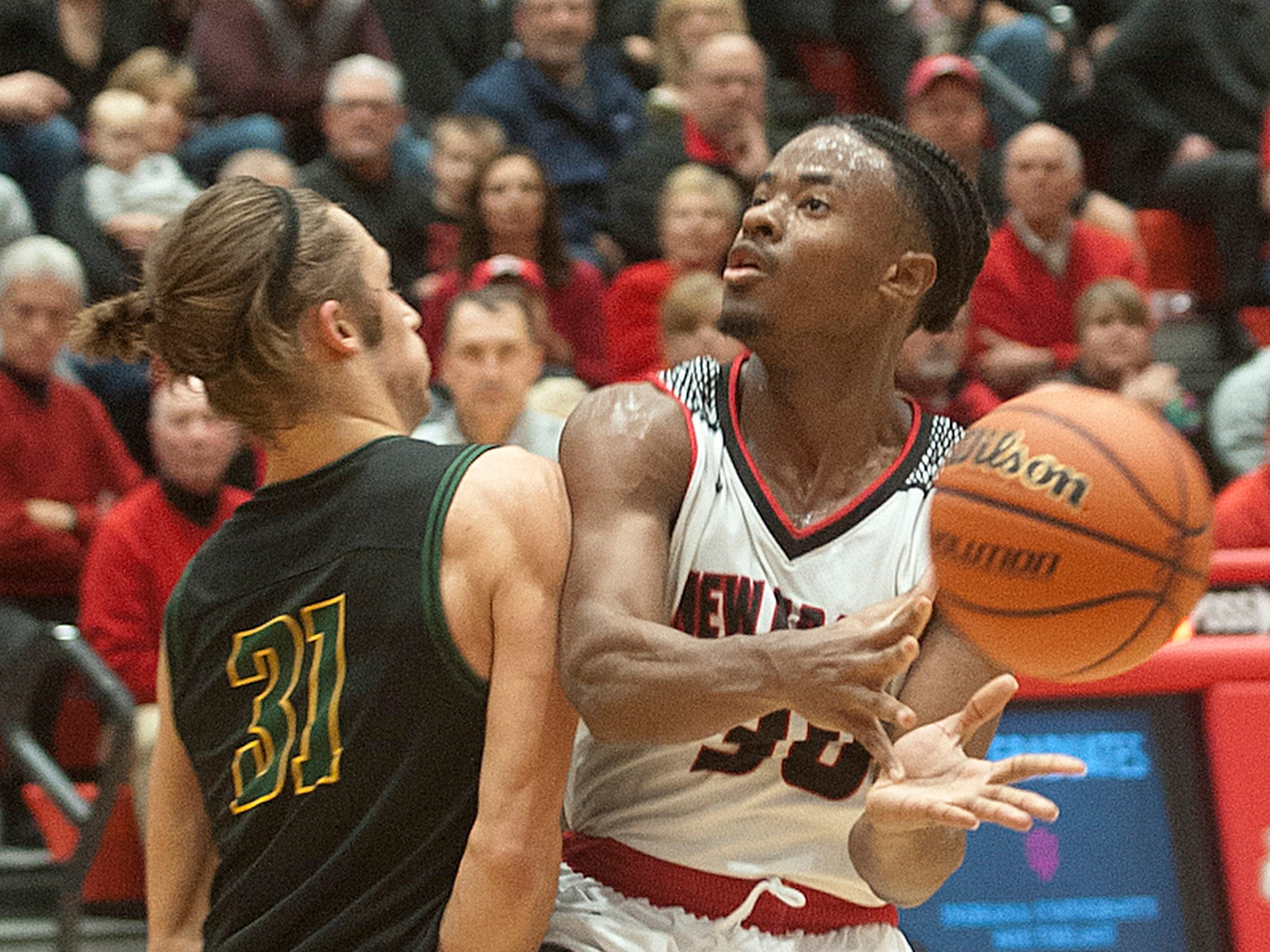 New Albany guard Julien Hunter gets the charging call after crashing into Floyd Central forward Cam Sturgeon. 07 December 2018