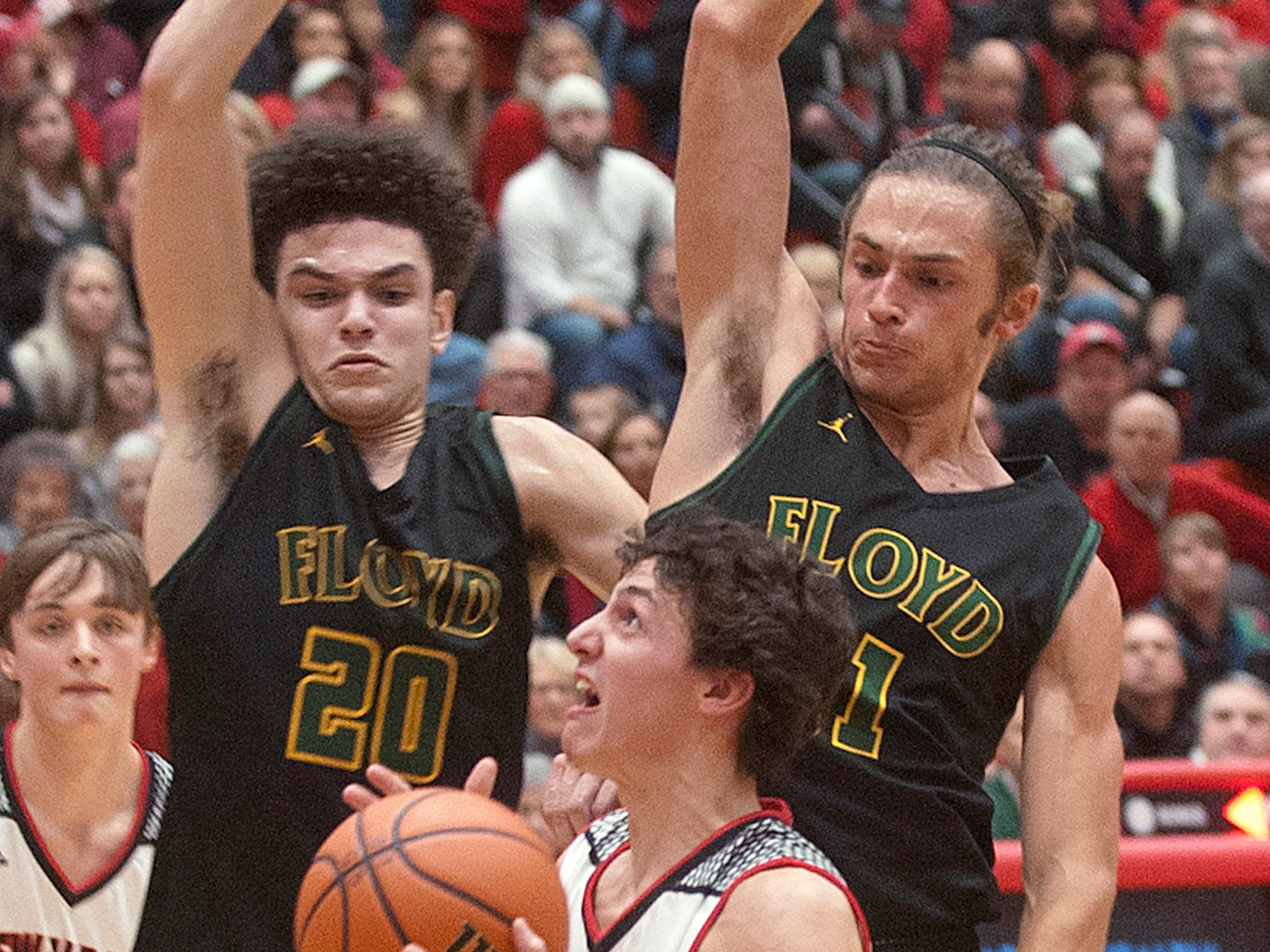 Floyd Central guard Gabe Cora, top left, and Floyd Central forward Cam Sturgeon, top right, try to stop the drive of New Albany guard Landon Sprigler. 07 December 2018