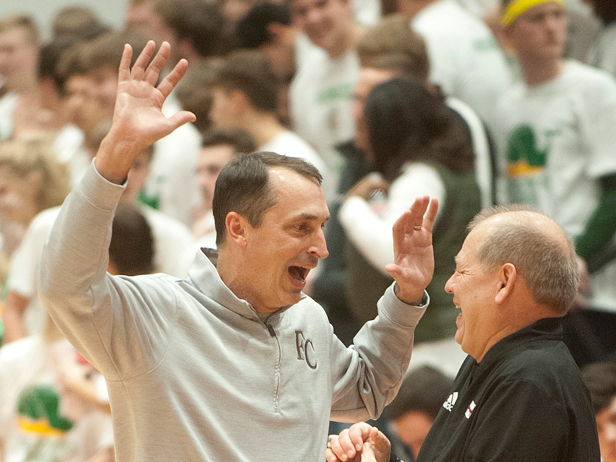 Floyd Central head basketball coach Todd Sturgeon jokes with New Albany head basketball coach Jim Shannon before the start of the game.07 December 2018