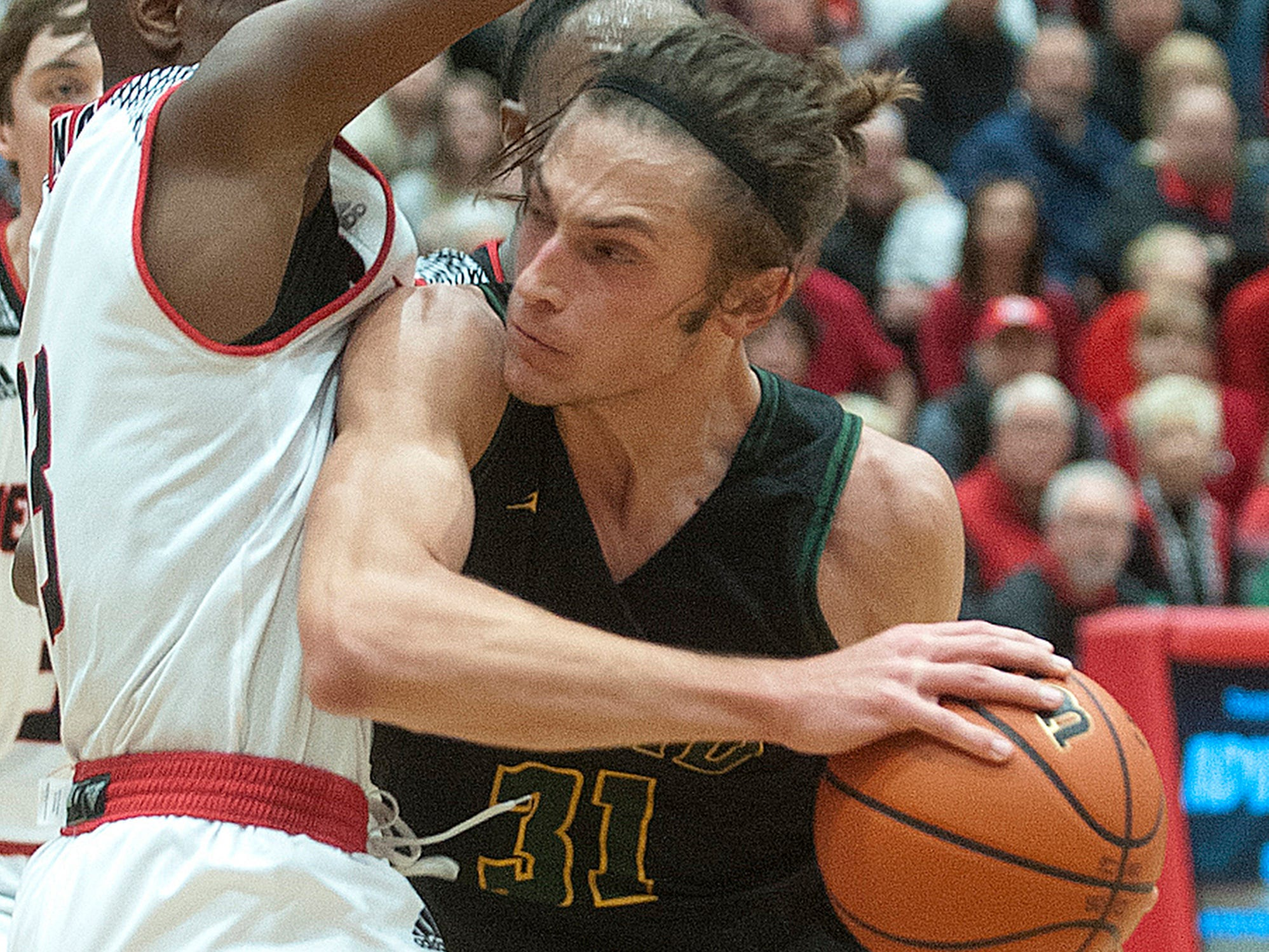 Floyd Central forward Cam Sturgeon makes contact with New Albany guard Chris Johnson on the way to the basket.07 December 2018