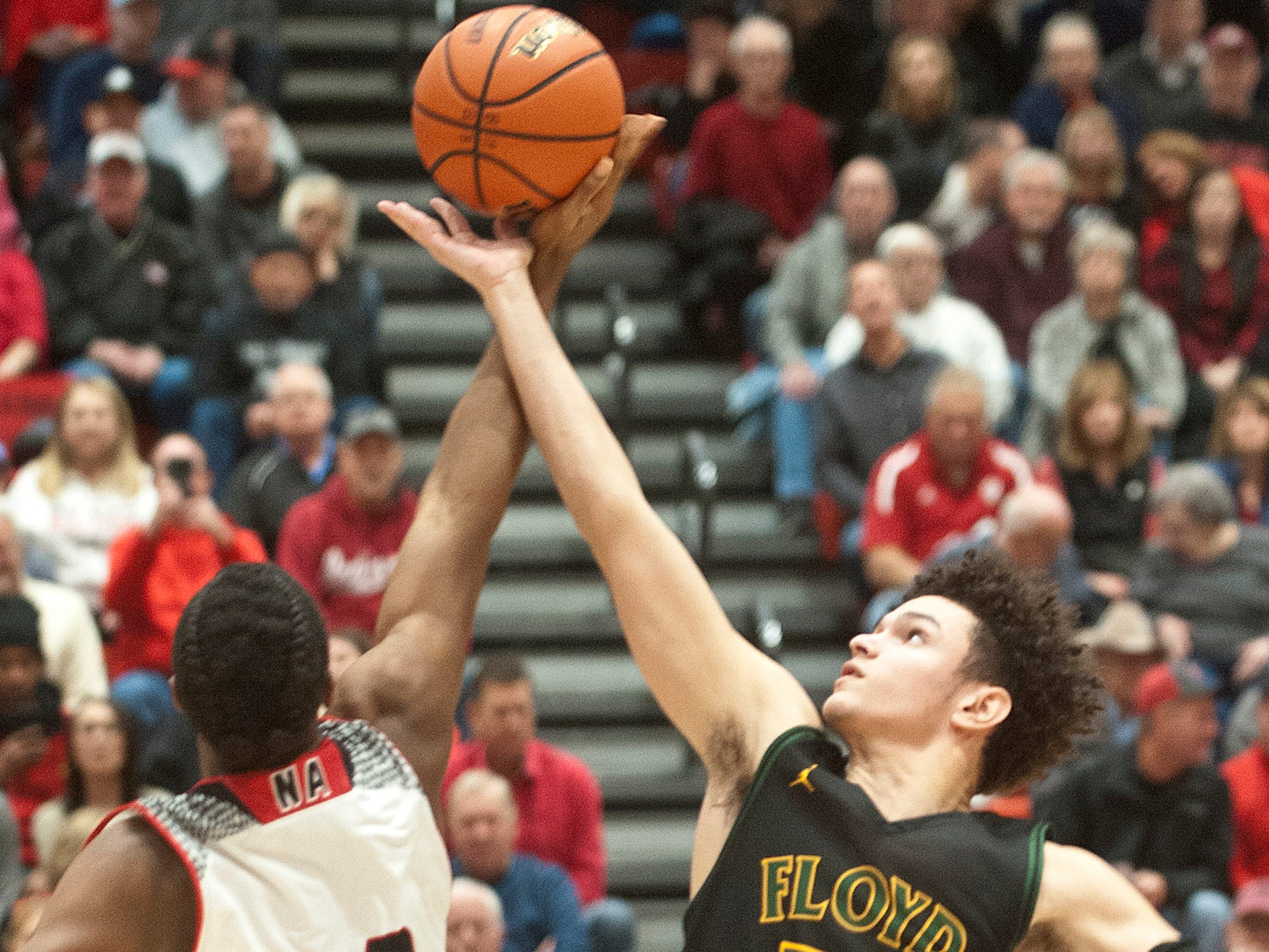 New Albany guard Julien Hunter and Floyd Central forward Cobie Barnes tip off the game.07 December 2018