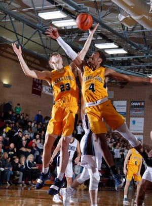 Grand Ledge's William Jerzak, left, and Stephon Hall reach for a rebound against Okemos, Friday, Dec. 7, 2018, in Okemos, Mich.