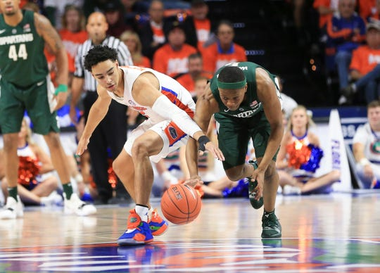 Florida guard Andrew Nembhard (2) and Michigan State guard Cassius Winston (5) go after the ball during the first half of an NCAA college basketball game Saturday, Dec. 8, 2018, in Gainesville, Fla.