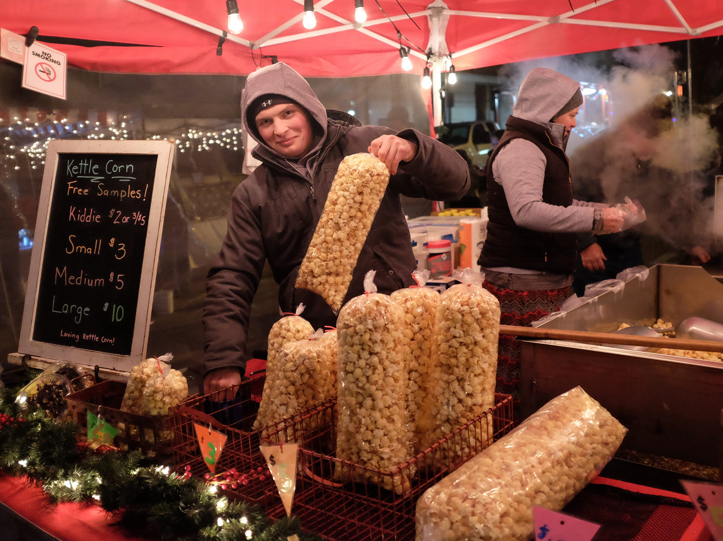 Taylor Haynes from Superior Kettle Corn serves up a bag during the Annual Festival of Lights and Santa Parade in St. Johns Friday, Dec, 7, 2018.