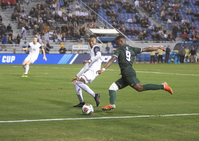Michigan State freshman Farai Mutatu (9) readies to kick the ball as he's defended by an Akron player during the College Cup on Friday, Dec. 8, 2018.