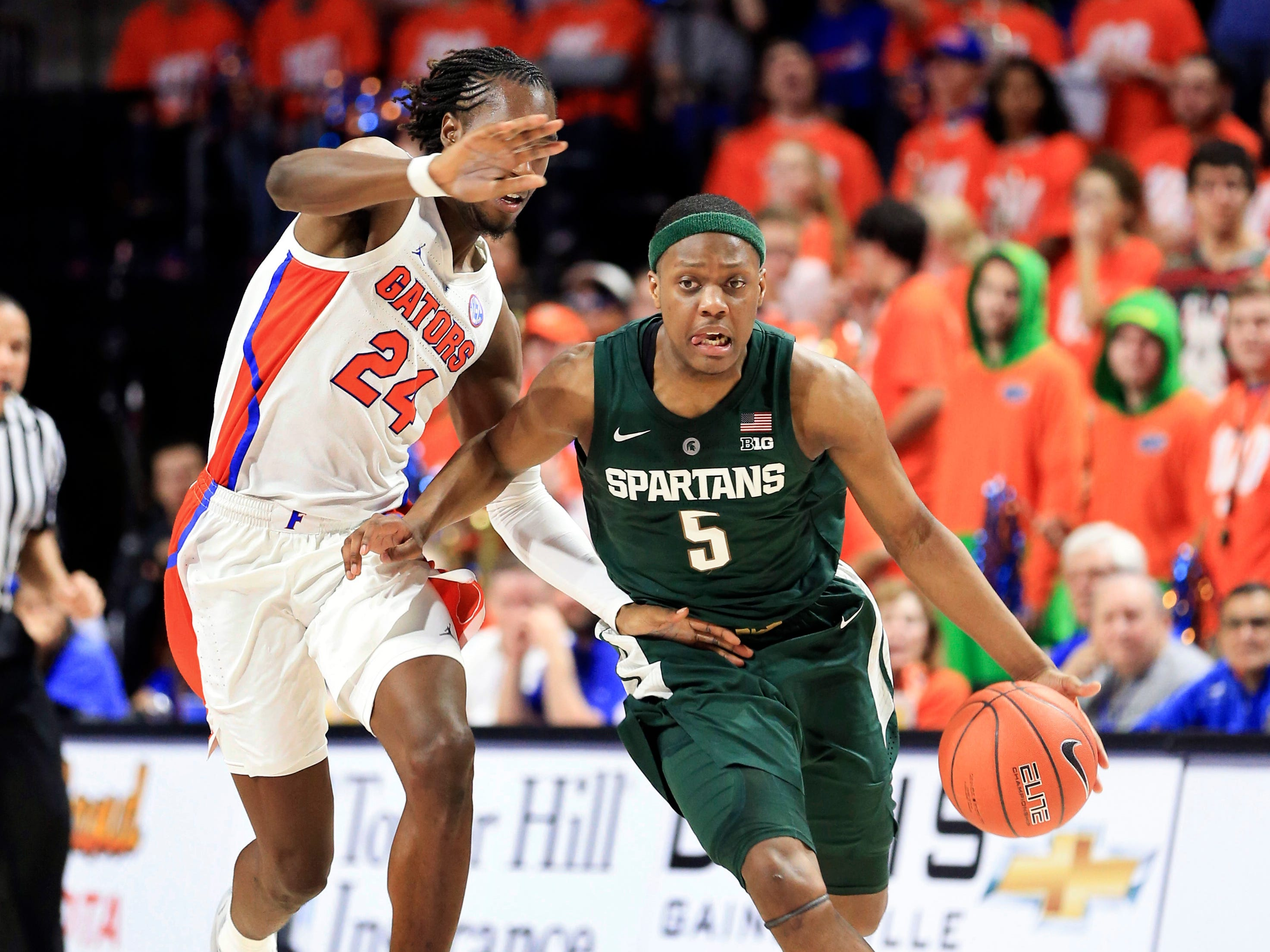 Michigan State guard Cassius Winston (5) dribbles up court past Florida guard Deaundrae Ballard (24) during the first half of an NCAA college basketball game Saturday, Dec. 8, 2018, in Gainesville, Fla.