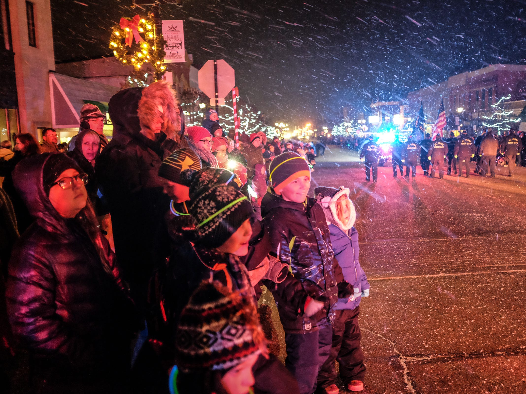 The driving snow doesn't bother these youngsters as they watch the Annual Festival of Lights and Santa Parade in downtown St. Johns Friday, Dec. 7, 2018.