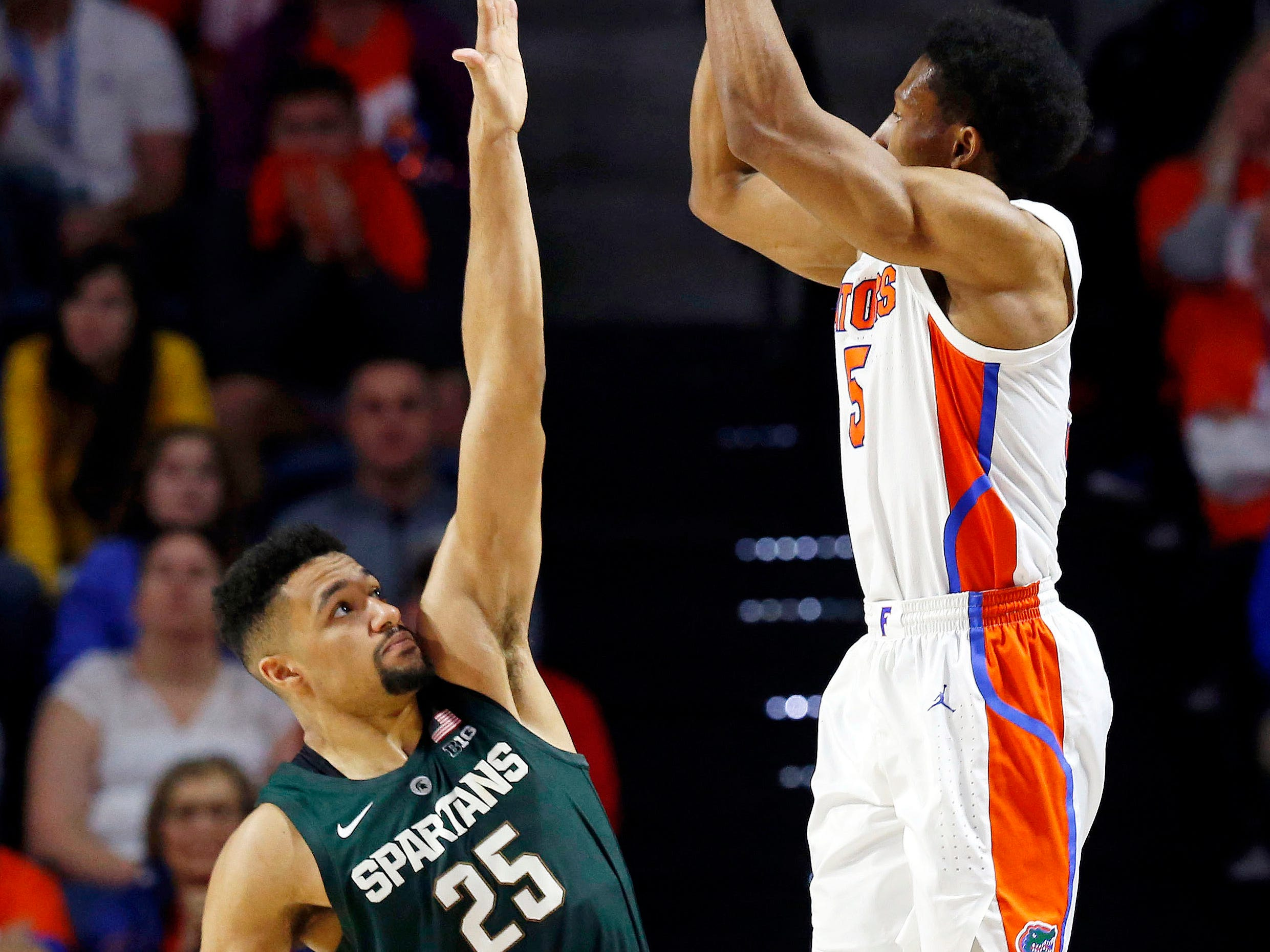 Florida Gators guard KeVaughn Allen (5) shoots over Michigan State Spartans forward Kenny Goins (25) during the second half at Exactech Arena.