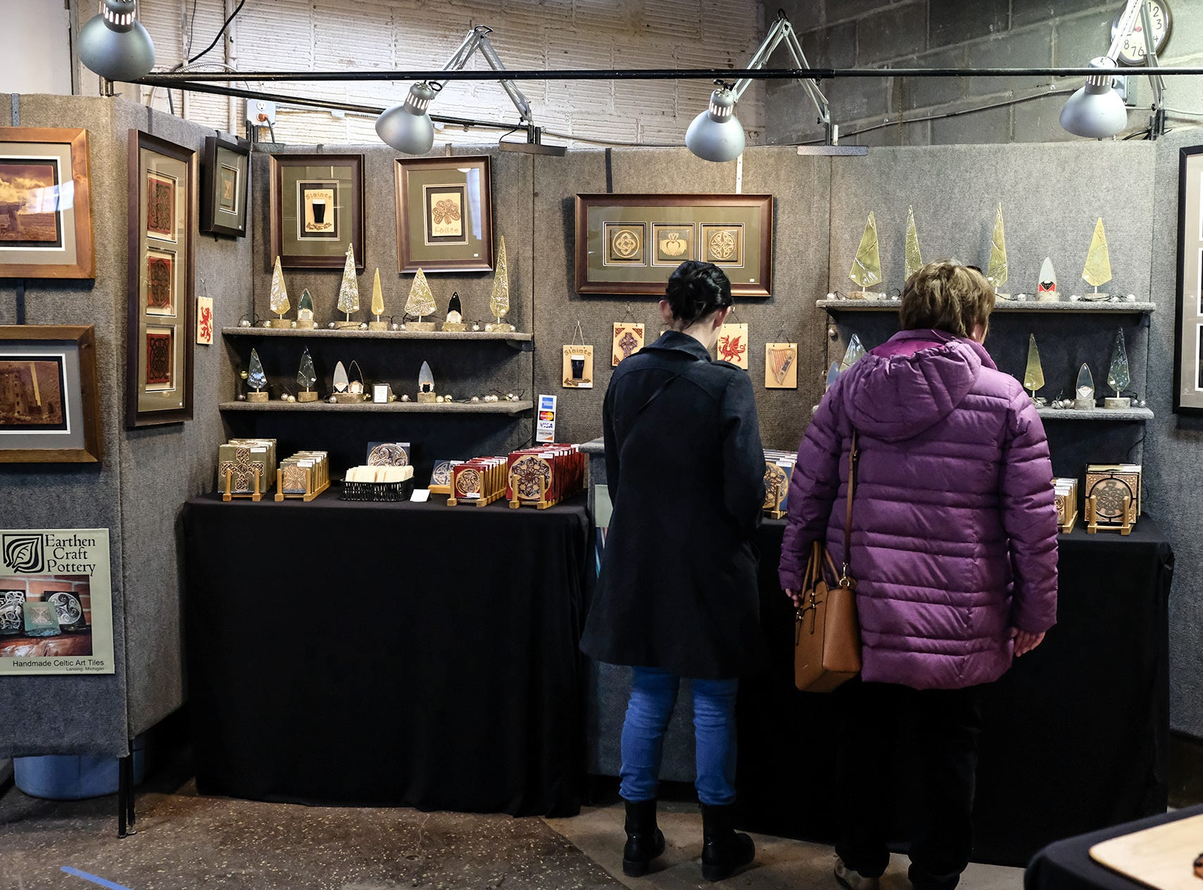 Two women look over the Earthen Craft Pottery display at the Reo Town Marketplace Saturday, Dec. 8, 2018.