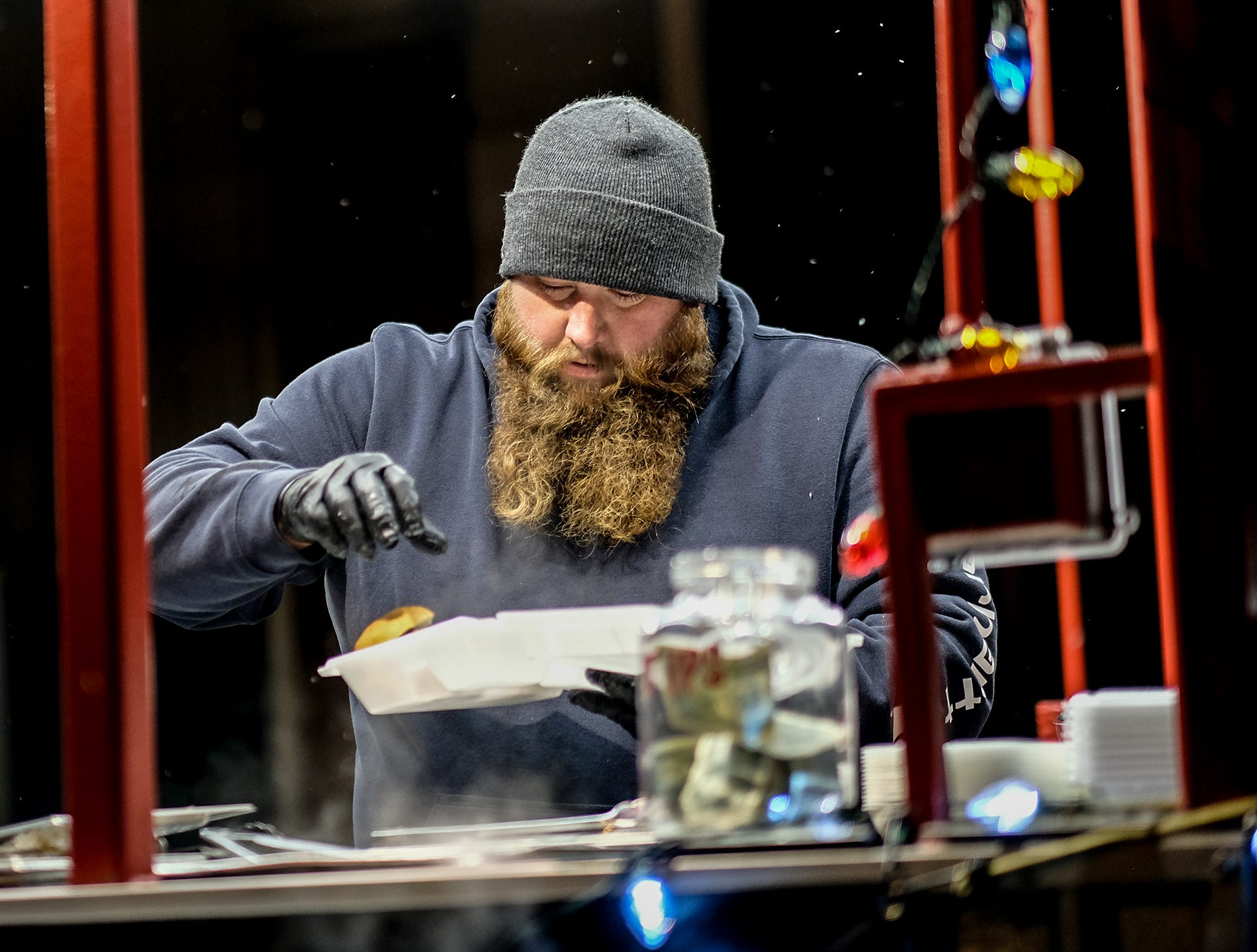 Dave Arnold from Clyde's Pit serves up some food at the Annual Festival of Lights and Santa Parade in downtown St. Johns Friday, Dec, 7, 2018.